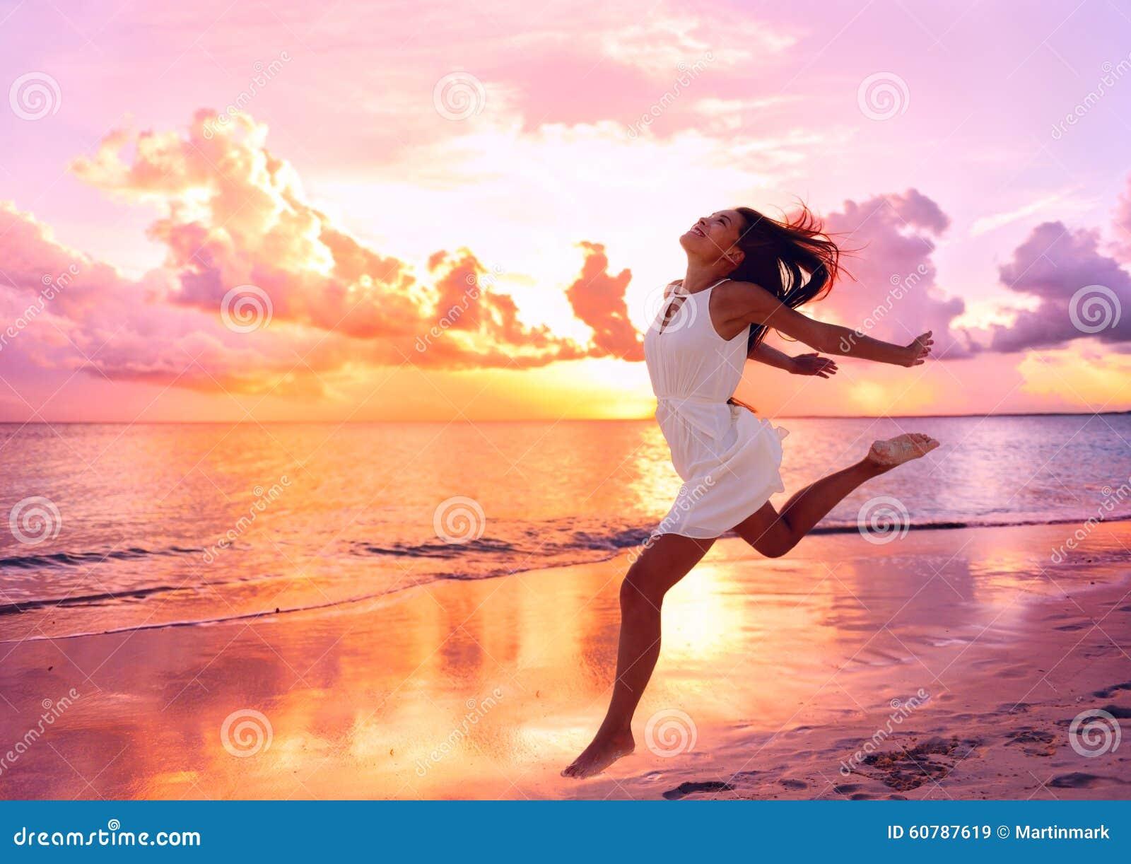 Mujer hermosa feliz que corre en la puesta del sol de la playa