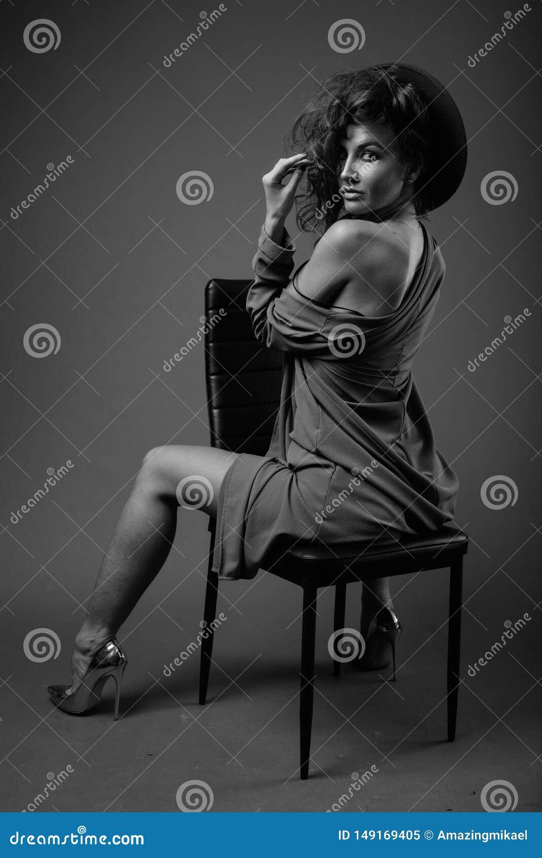 Mujer hermosa joven con el pelo rizado que presenta en blanco y negro