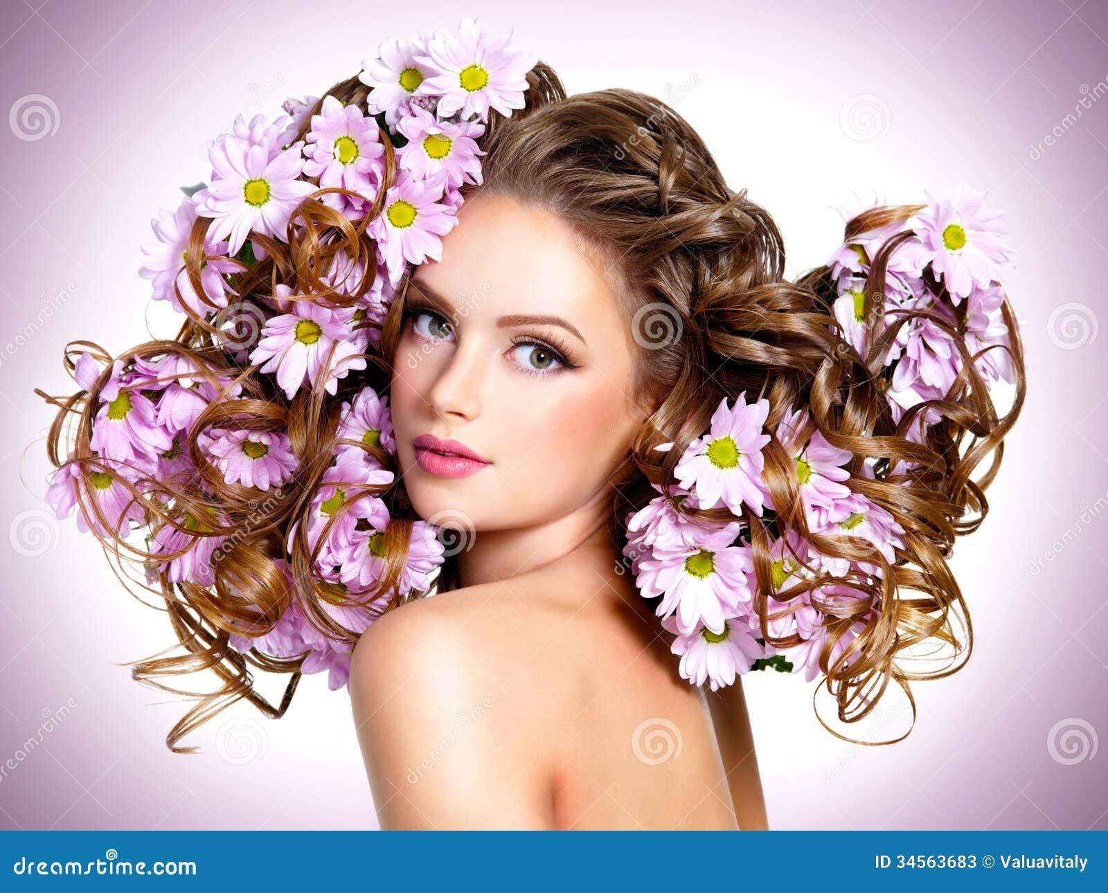 Mujer hermosa joven con las flores en pelos