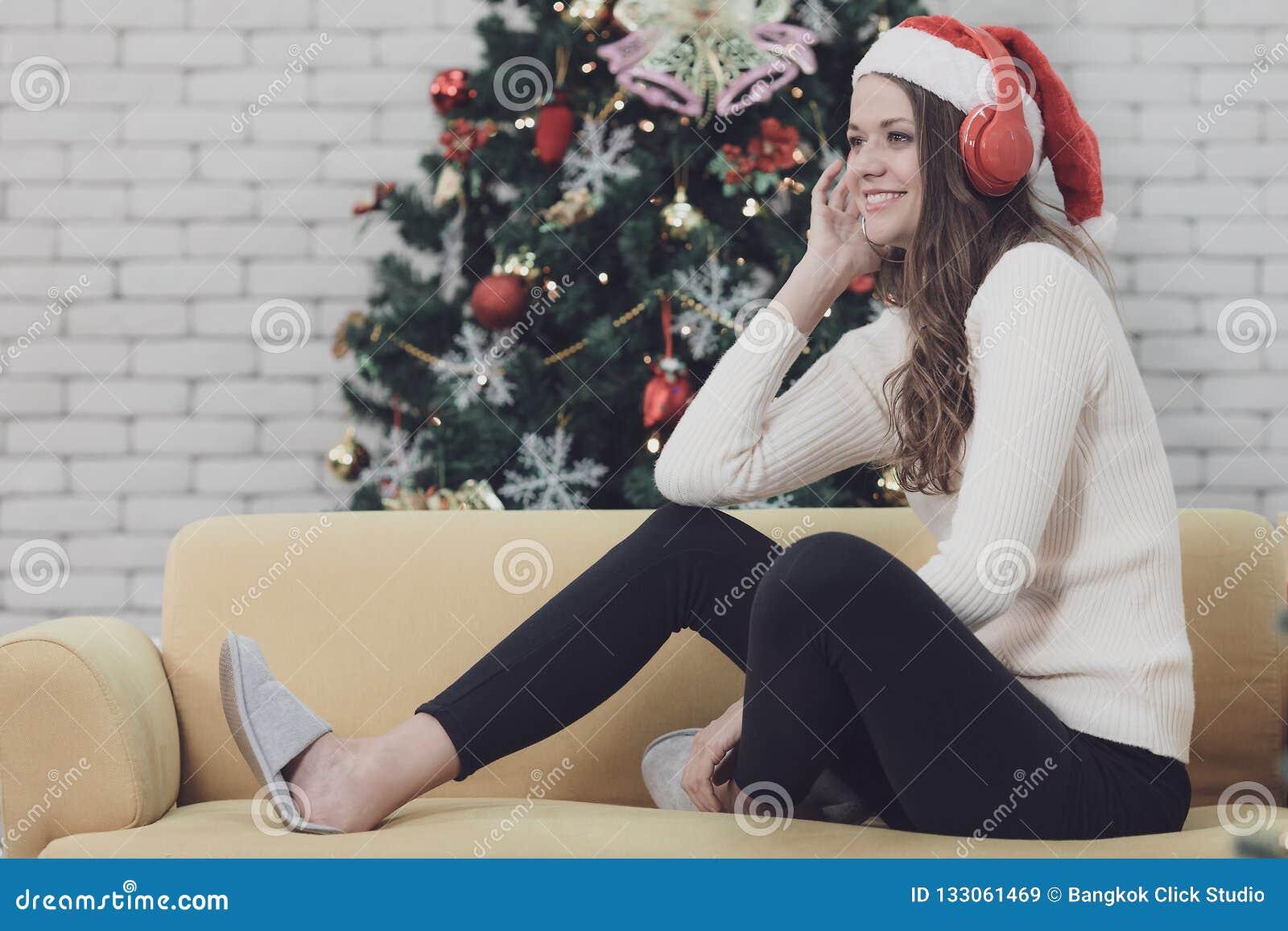Mujer hermosa joven en el sombrero rojo que se sienta en el sofá entre el christm