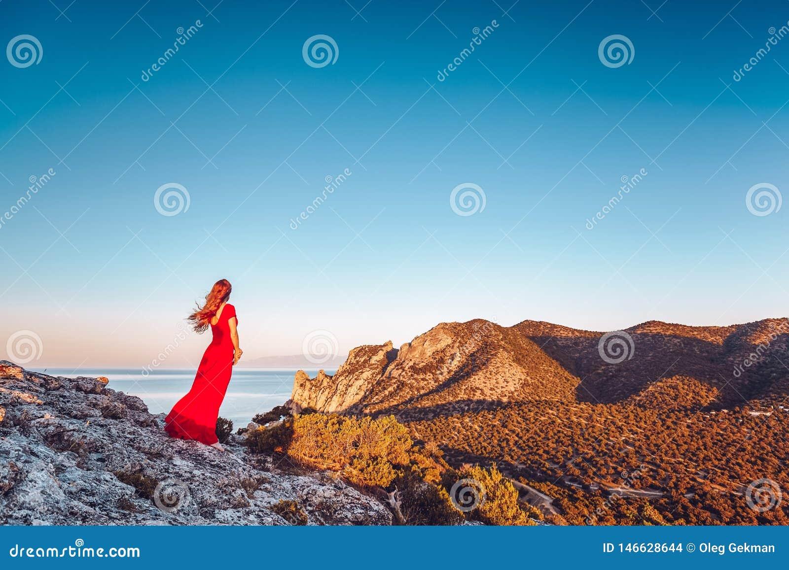 Mujer hermosa joven en el vestido rojo que mira al mar de las monta?as