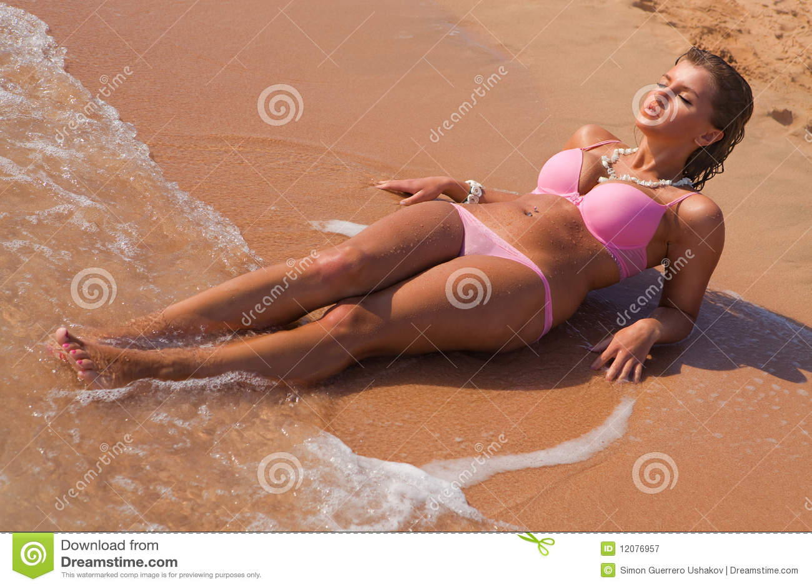 Mujer hermosa joven en la colocación rosada del bikiní