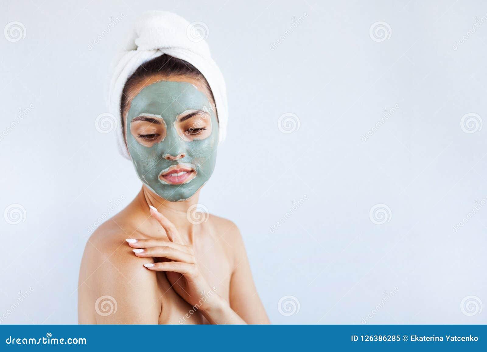 Mujer hermosa joven en mascarilla del fango azul terapéutico Spa