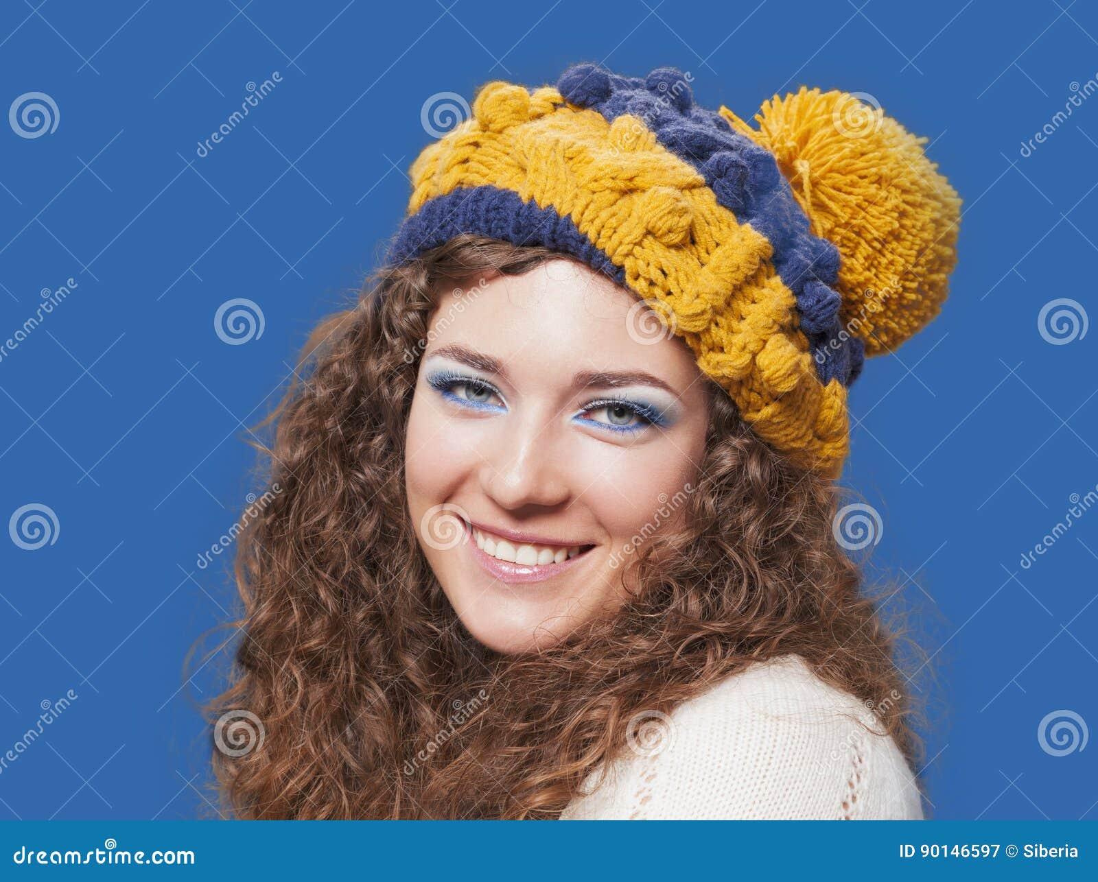 Mujer hermosa joven en sombrero divertido hecho punto