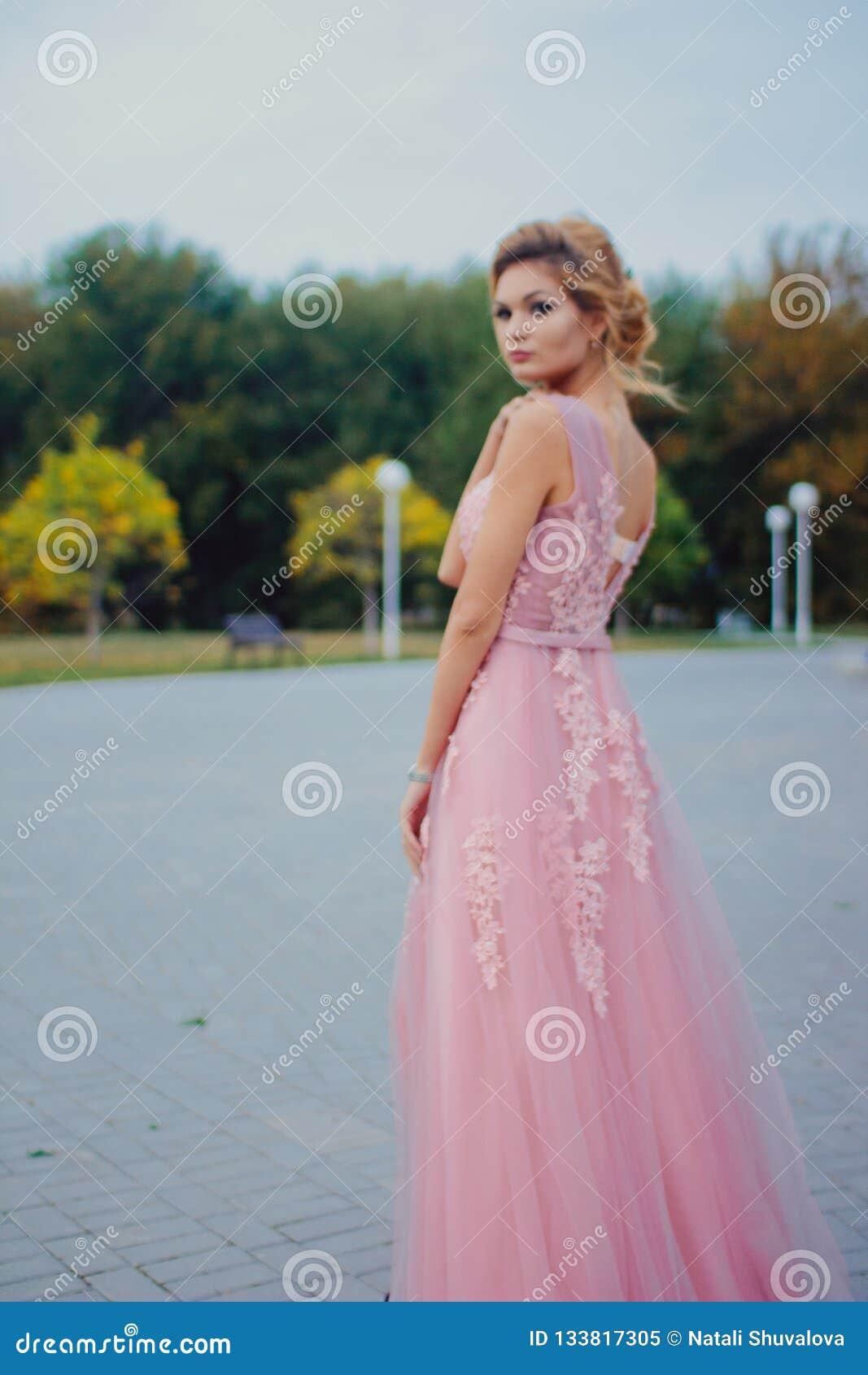 Mujer hermosa joven en trayectoria que camina rosada larga del vestido de noche en parque Forme el retrato del estilo de la mucha