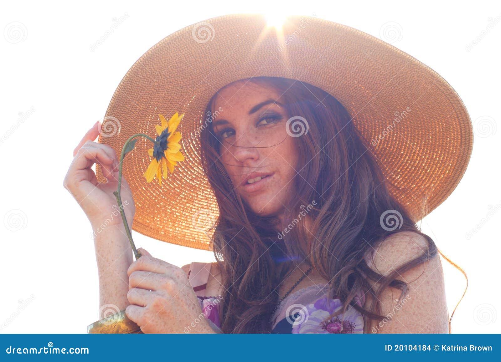 Mujer hermosa joven en un campo en tiempo de verano