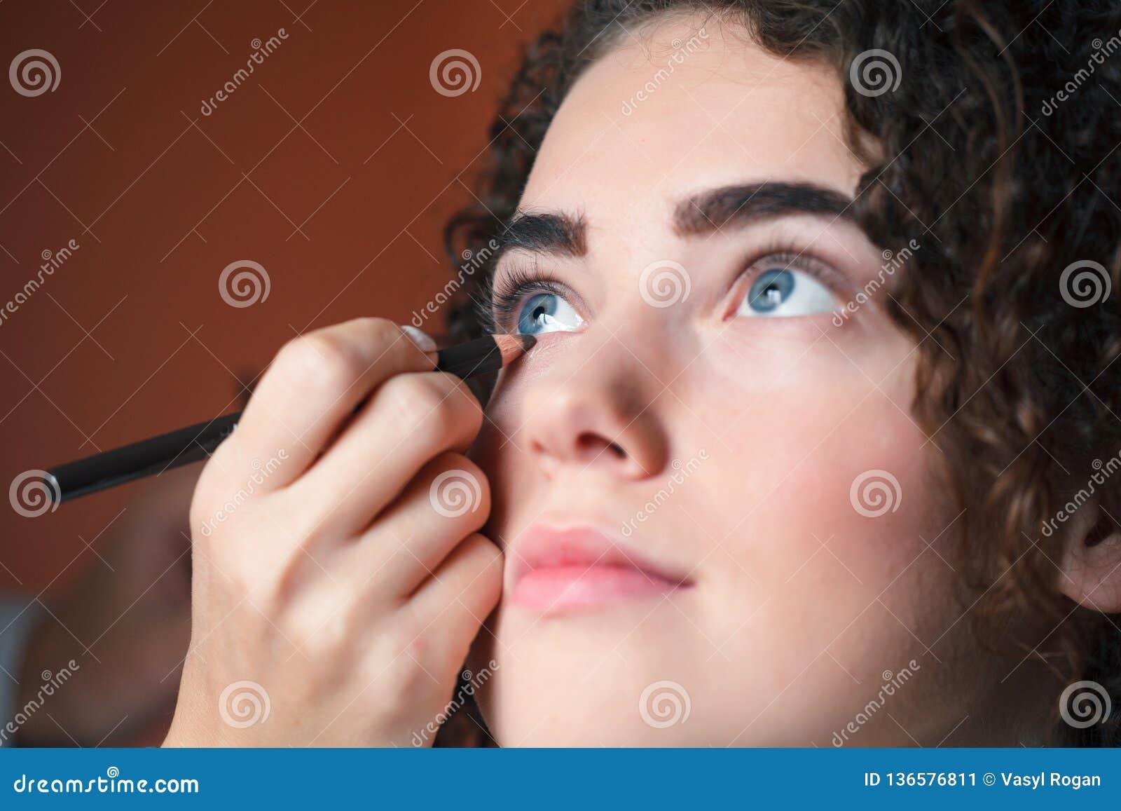 Mujer hermosa joven que aplica lápiz de ojos en el párpado con el lápiz