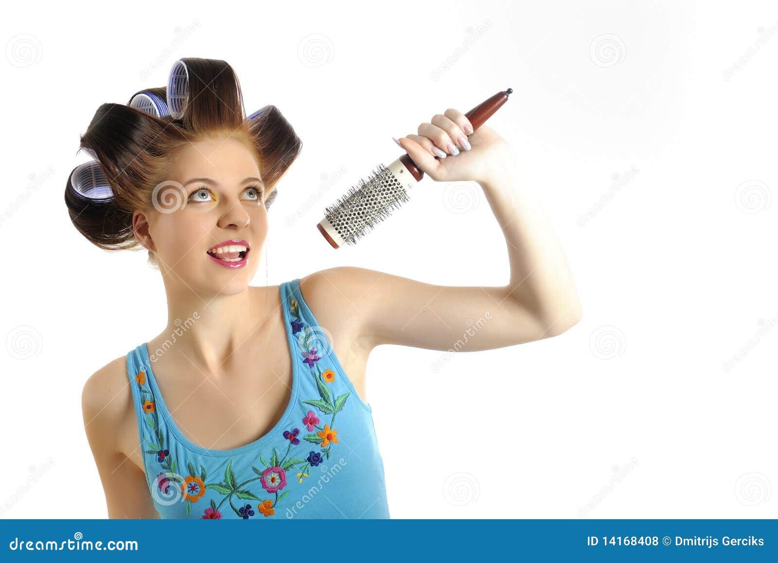 Mujer hermosa joven que canta al micrófono del cepillo mientras que  consigue su peinado hecho con los bigudíes en su pelo. aislado en el fondo  blanco. ... 864dea66983e