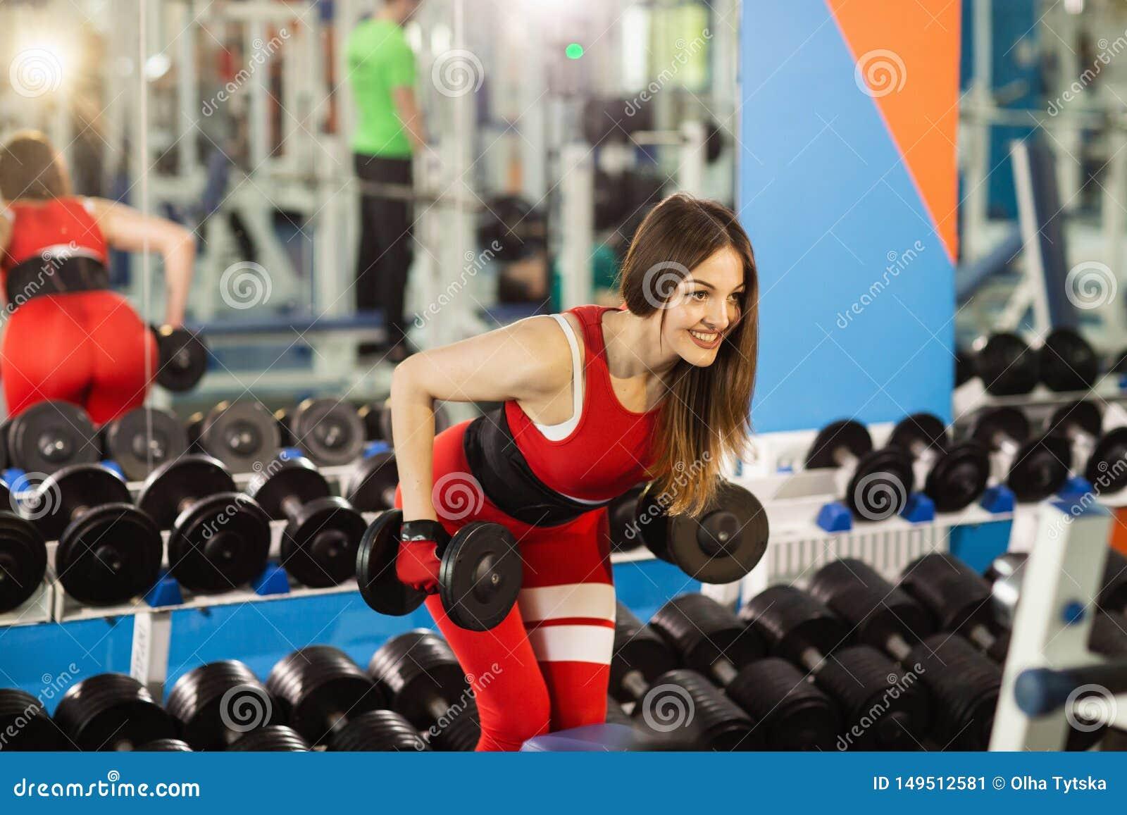 Mujer hermosa joven que hace ejercicios con pesa de gimnasia en gimnasio La muchacha sonriente alegre est? gozando con su proceso