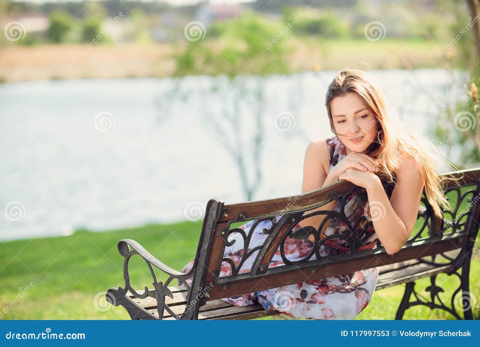 0a618fc2de17 Mujer hermosa joven que se sienta en banco en muchacha bonita del parque en  el aire
