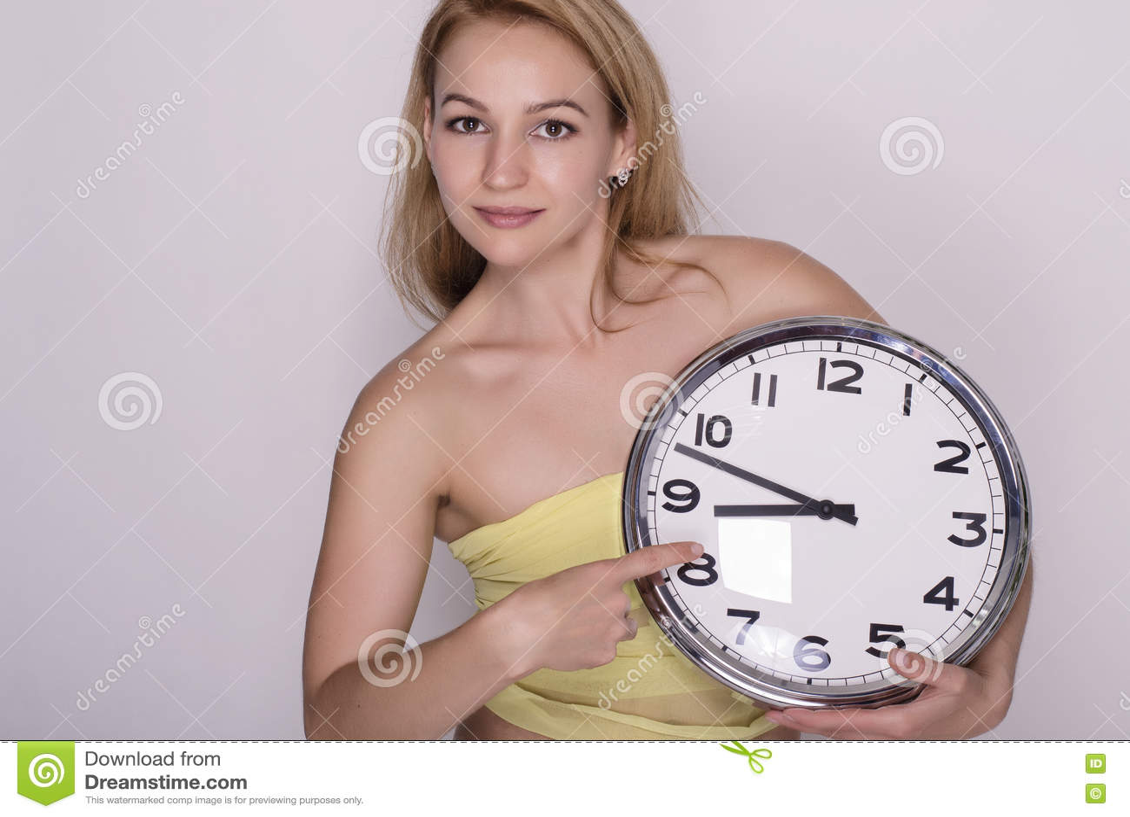 Mujer hermosa joven que sostiene el reloj grande Mida el tiempo del concepto
