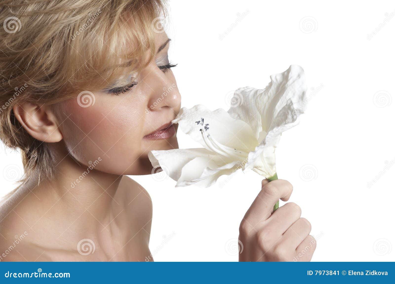 Mujer hermosa para oler la flor. cierre para arriba