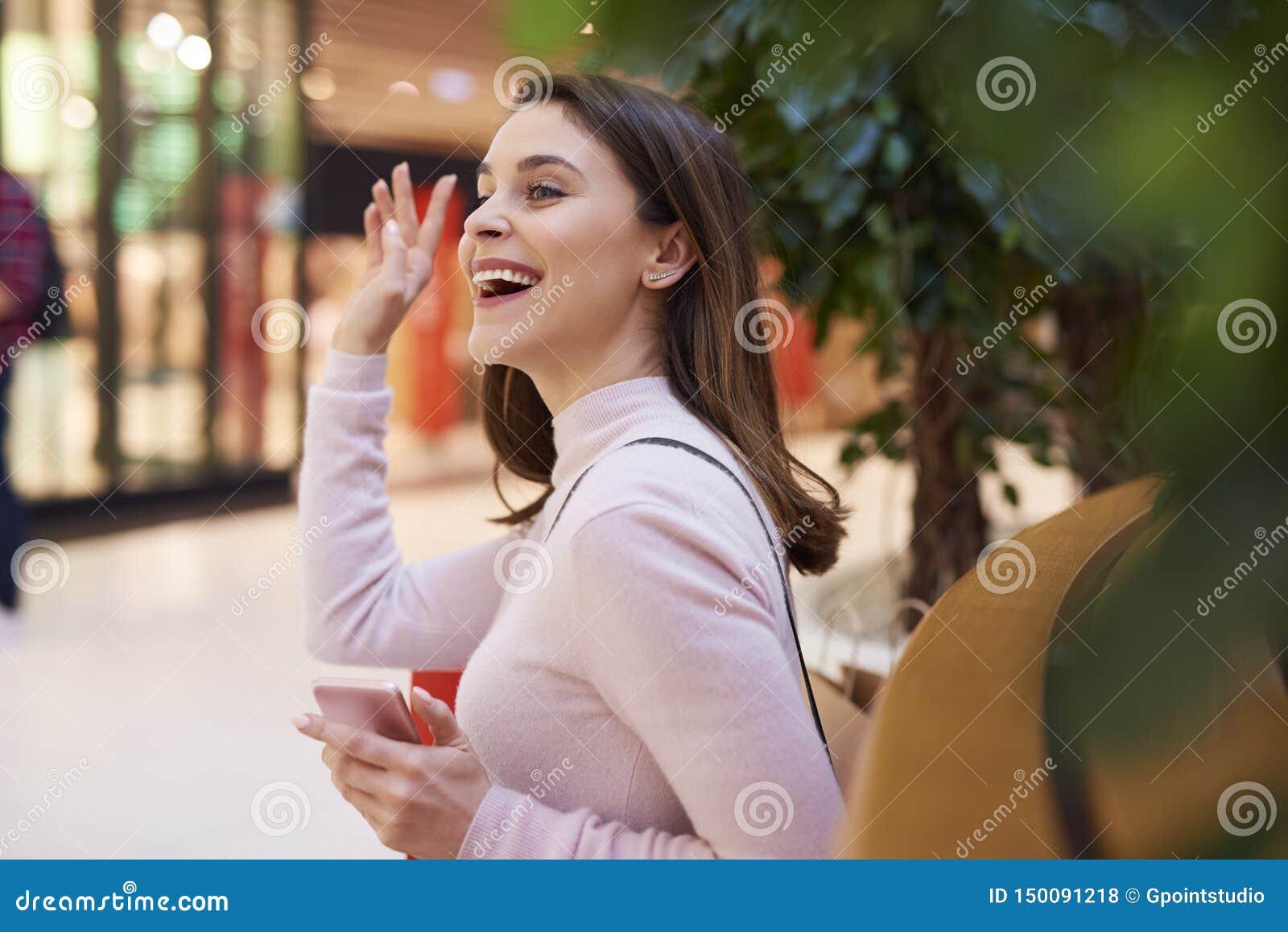 Mujer hermosa que dice hola y que agita su mano