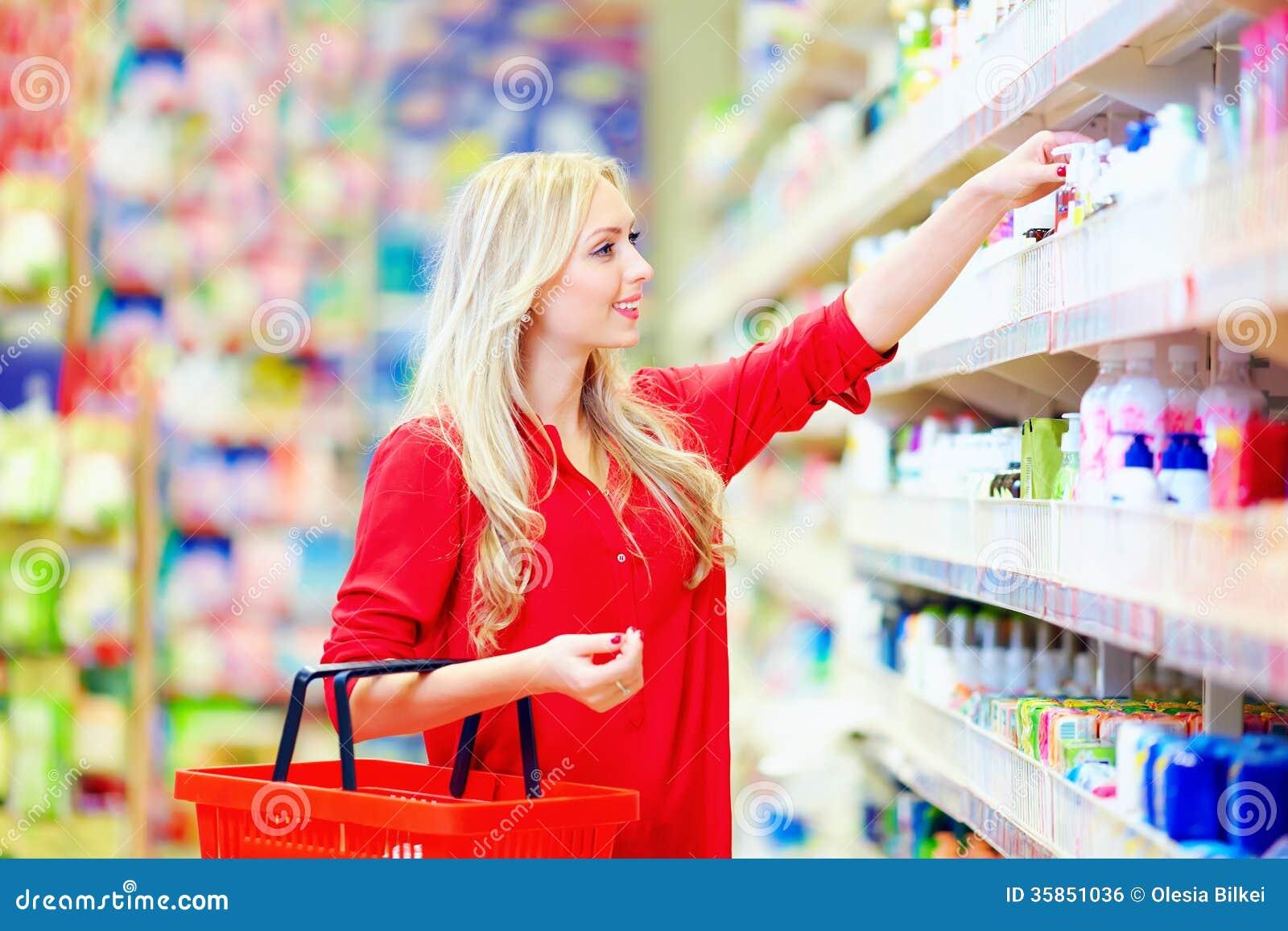 Mujer hermosa que elige el producto del cuidado personal en supermercado