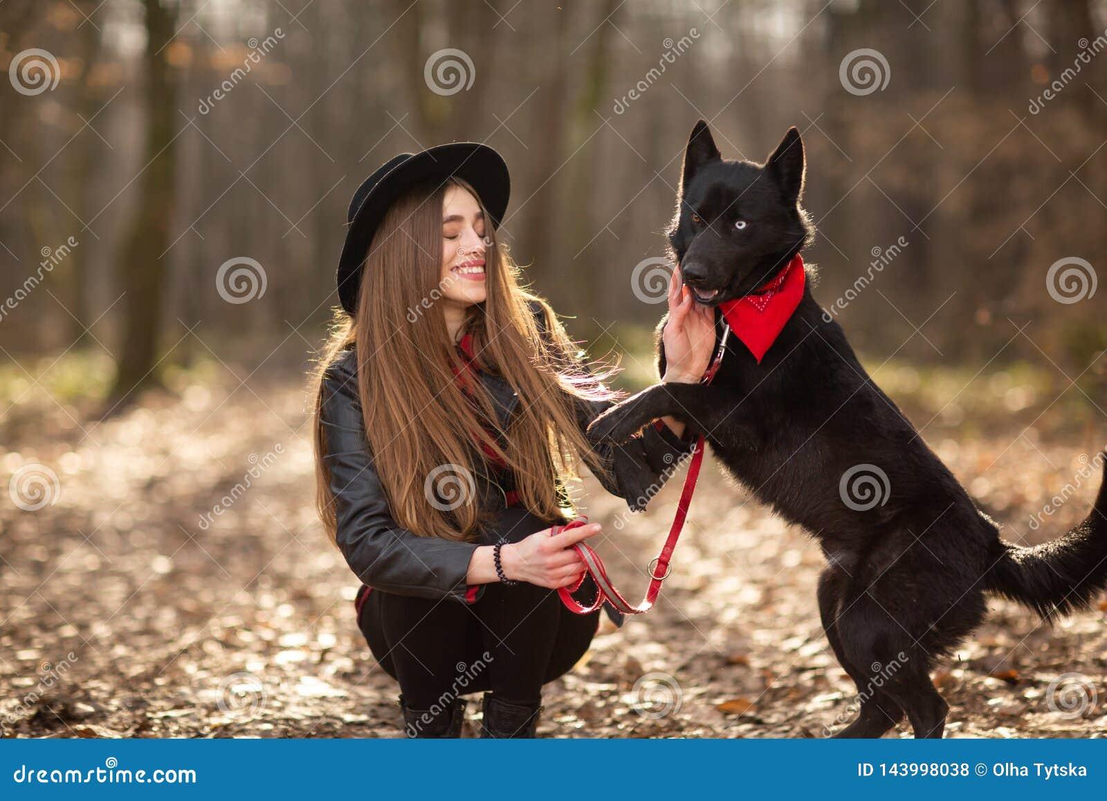 Mujer hermosa que frota ligeramente su perro al aire libre Muchacha bonita que juega y que se divierte con su animal doméstico po
