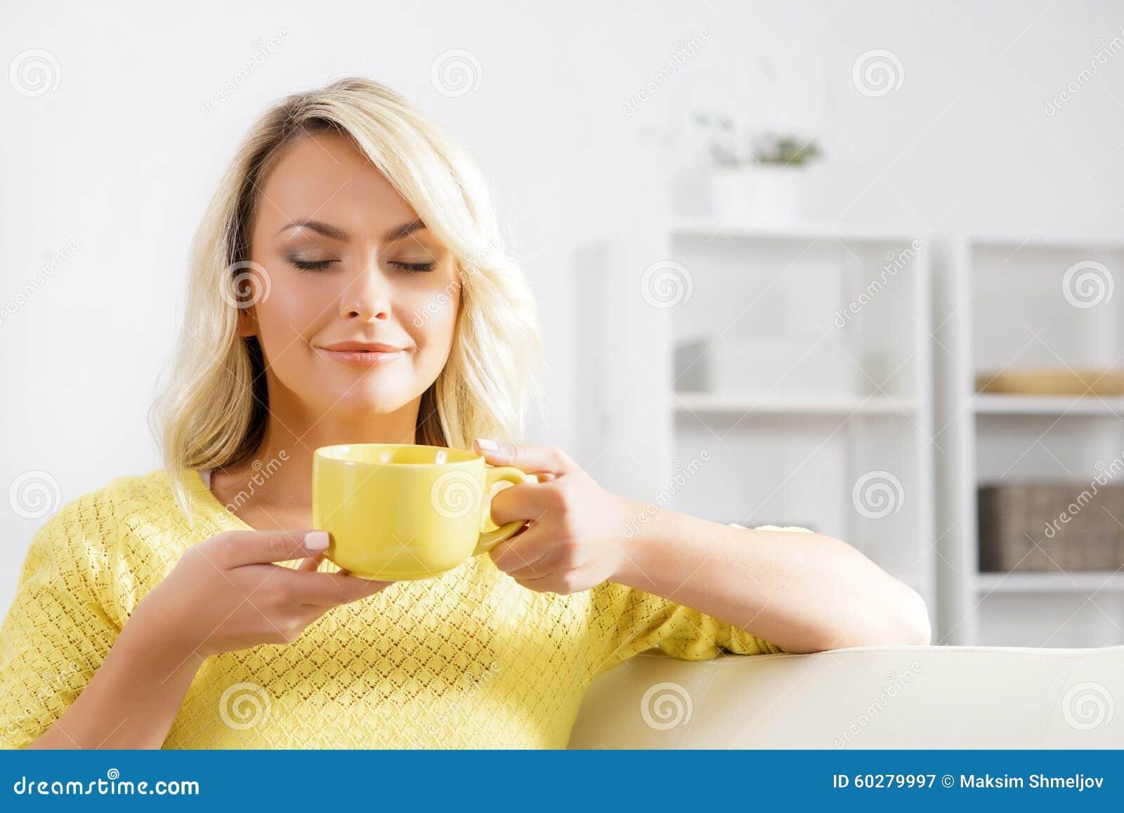 Mujer hermosa que goza del olor del café