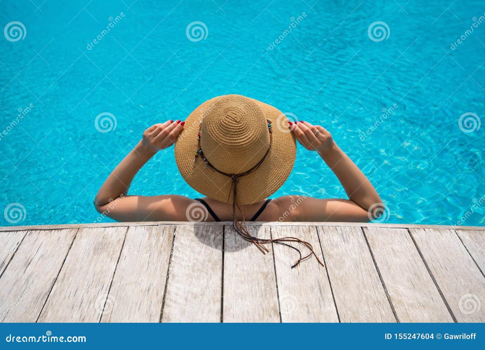 Mujer hermosa que goza en la piscina Muchacha que se relaja en piscina en d?a soleado caliente Vacaciones de verano id?licas Part