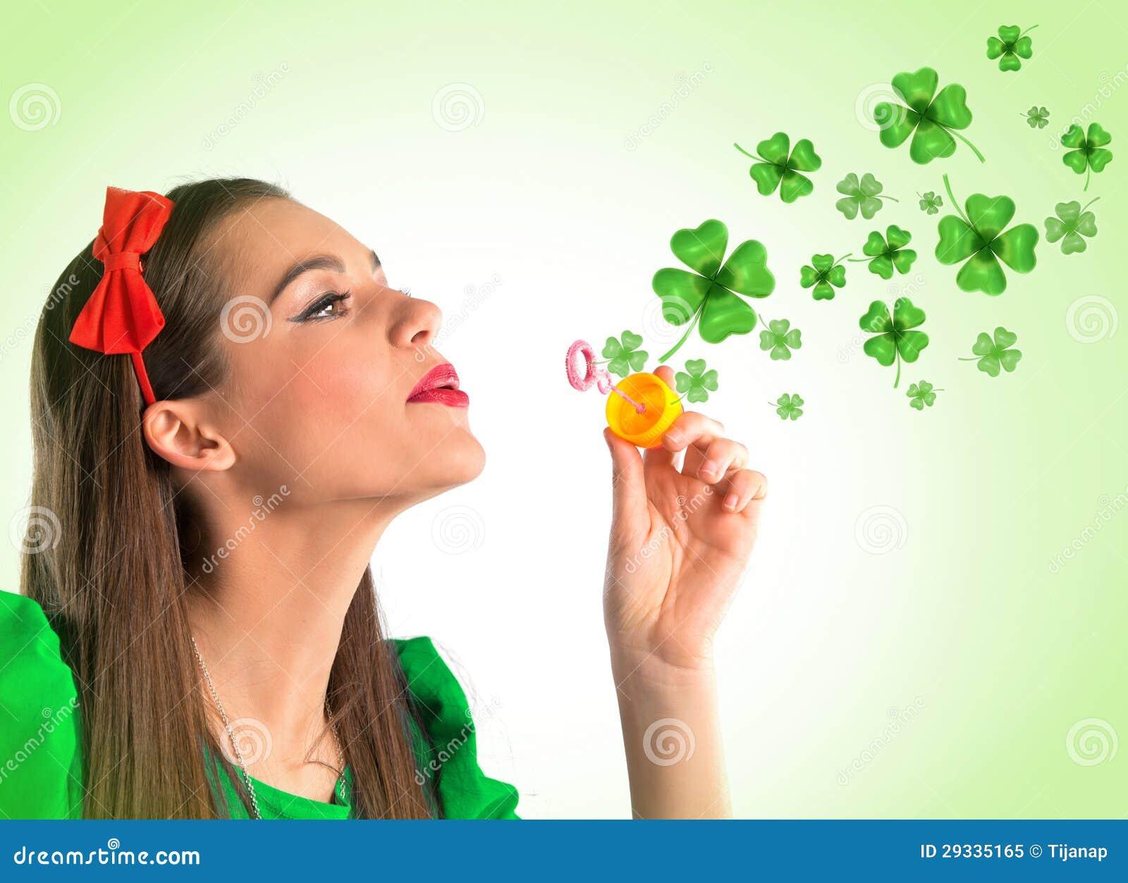 Mujer hermosa que hace cuatro burbujas del trébol de la hoja