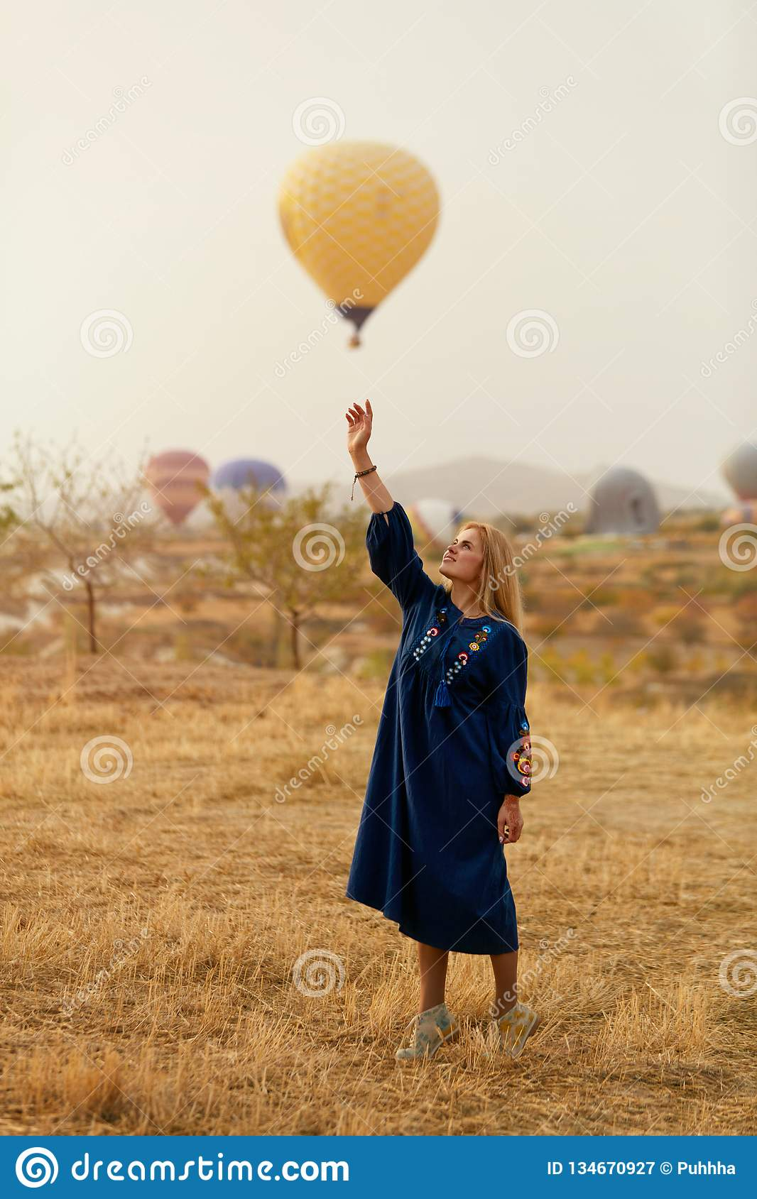 Mujer hermosa que intenta alcanzar el globo del aire caliente en cielo con la mano
