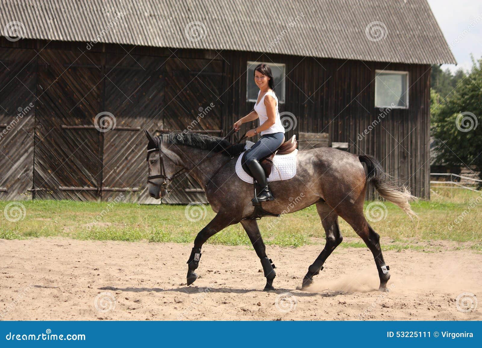 Mujer hermosa que monta el caballo gris