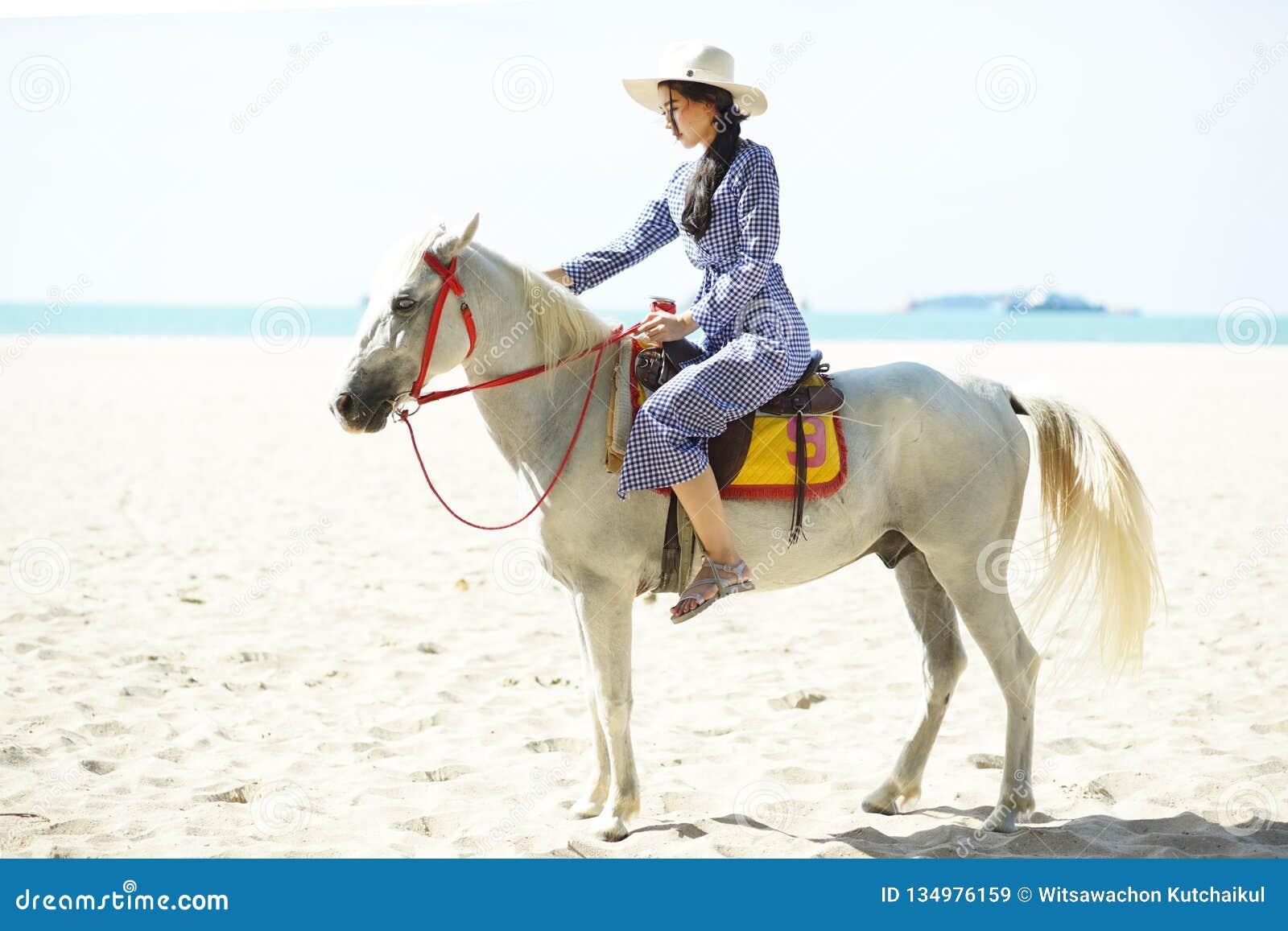 Mujer hermosa que monta un caballo en la playa
