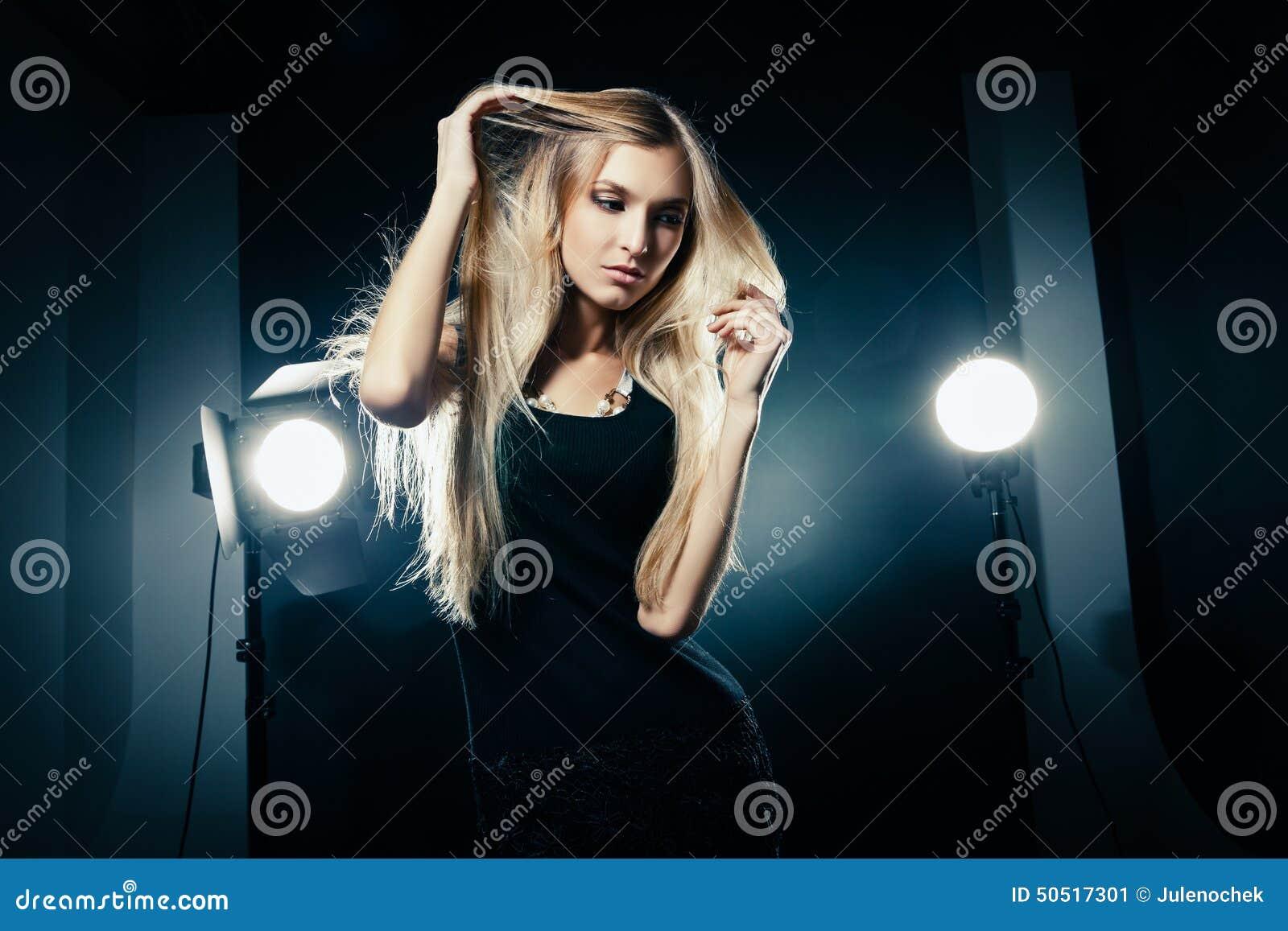 Mujer hermosa que presenta en el estudio en flashes ligeros