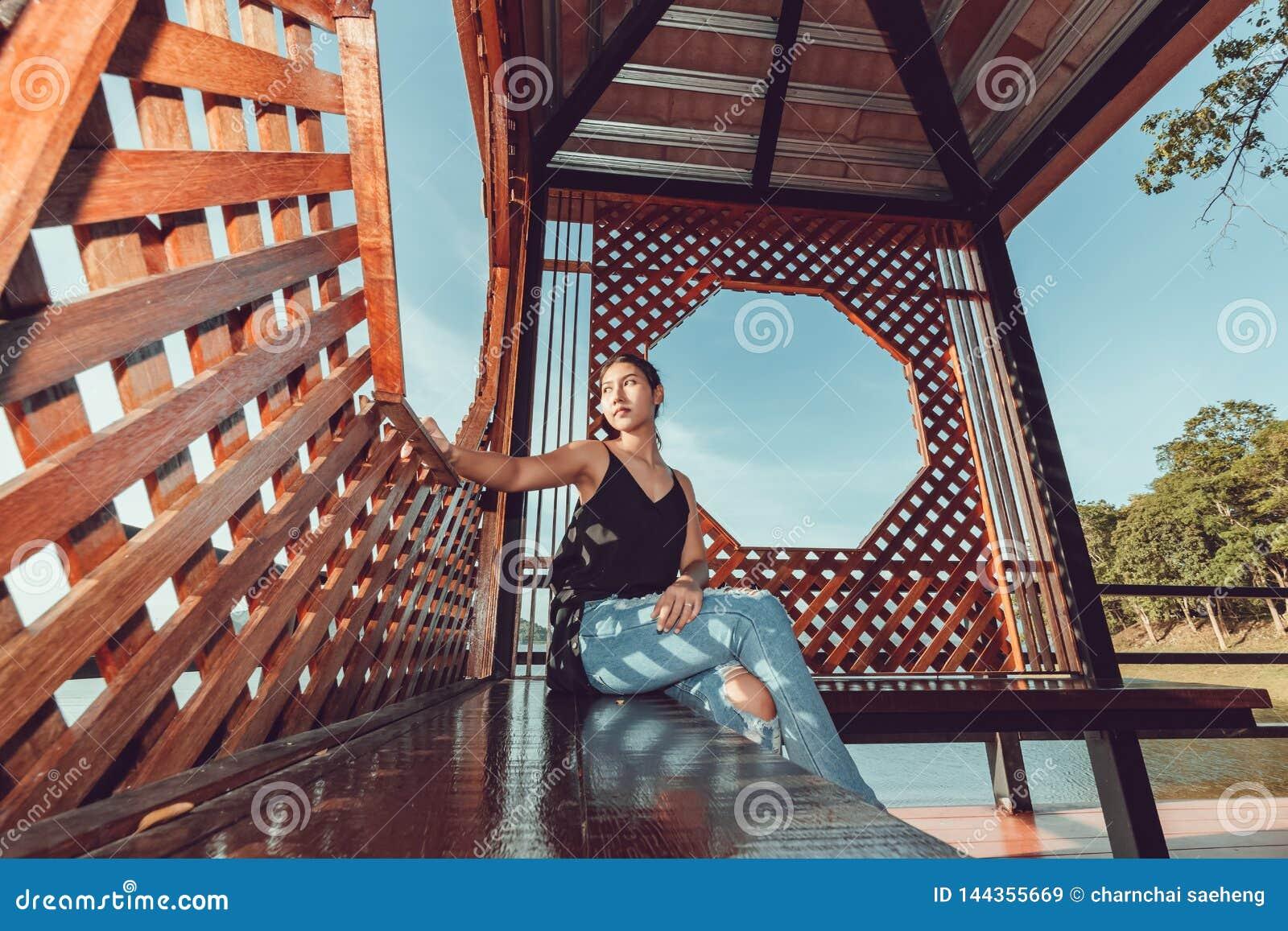 Mujer hermosa que se sienta en banco en muchacha bonita del parque en el aire libre en la naturaleza del d?a de verano