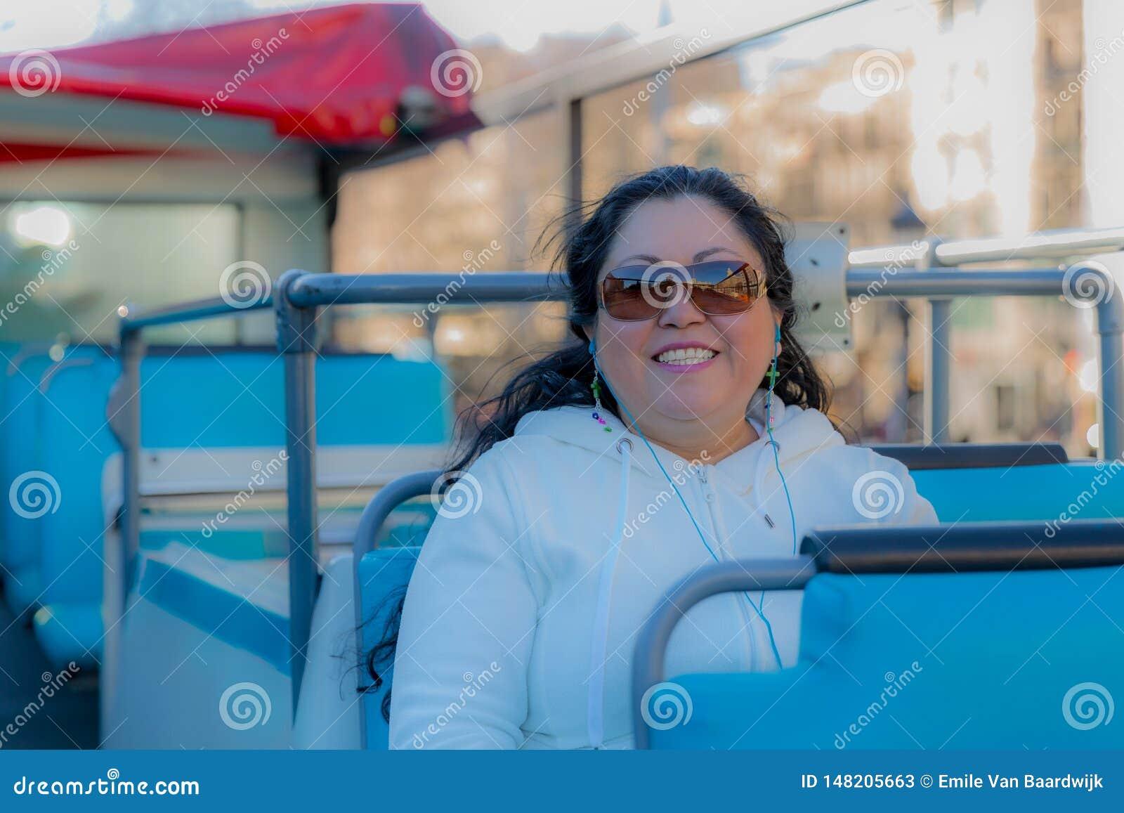 Mujer hermosa que sonríe en un autobús turístico que goza de la ciudad