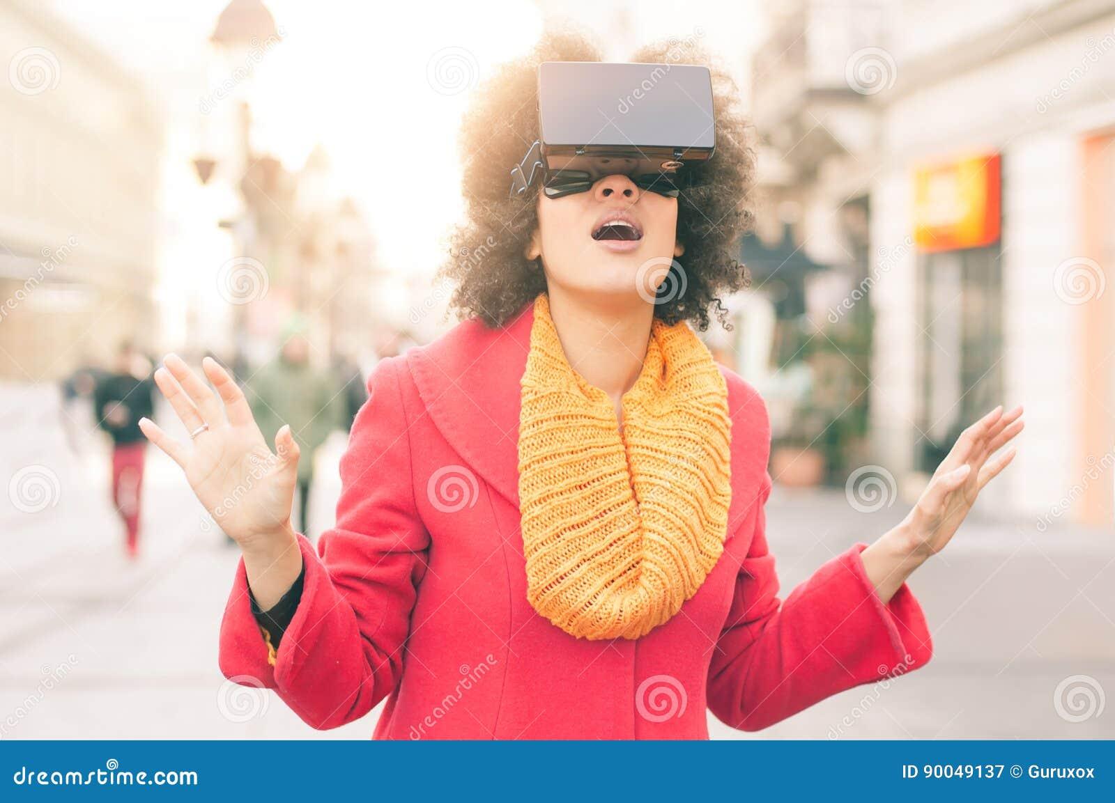 Mujer hermosa que usa los vidrios de alta tecnología de la realidad virtual al aire libre