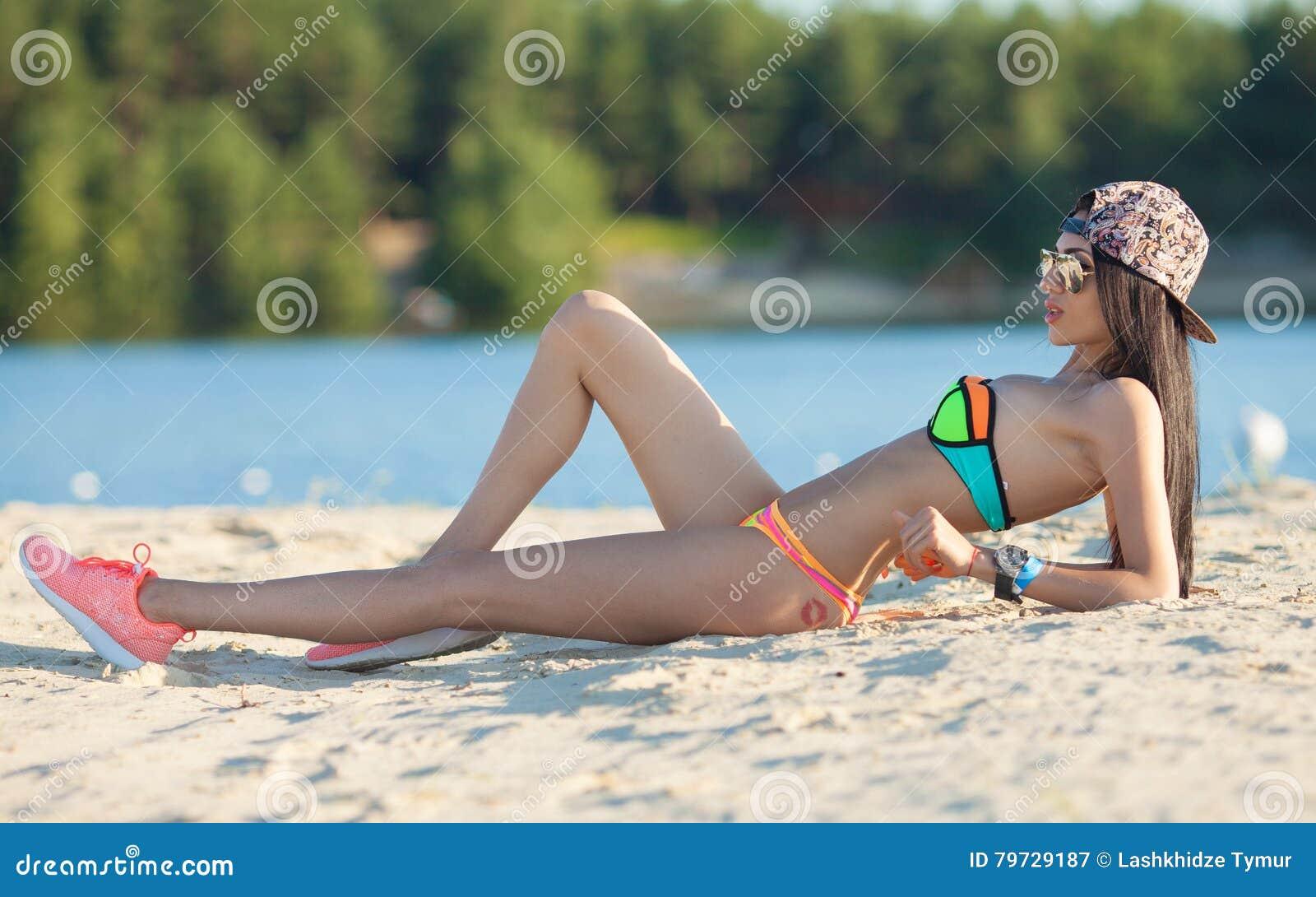 Mujer hermosa sonriente que toma el sol en una playa Foco en muchacha