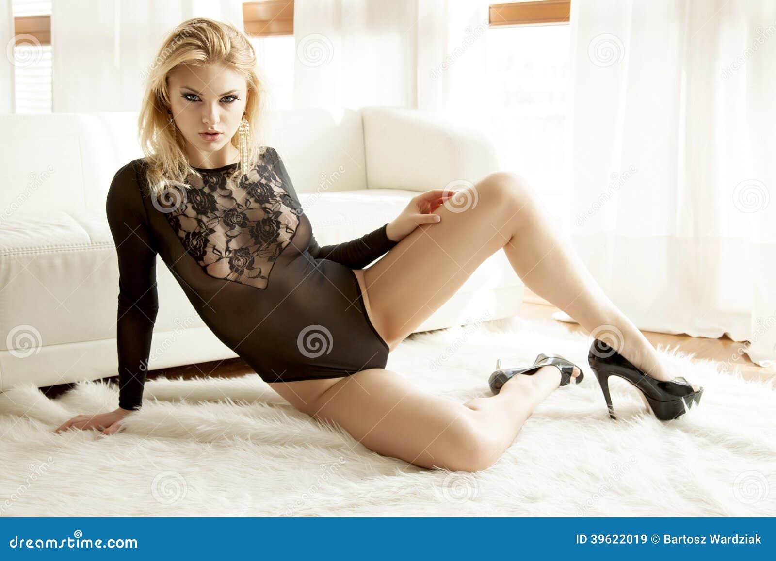 2a5bfdb0daf5 Mujer rubia de la sensualidad adulta joven hermosa y atractiva en ropa  interior transparente negra en el sofá blanco en el apartamento de lujo