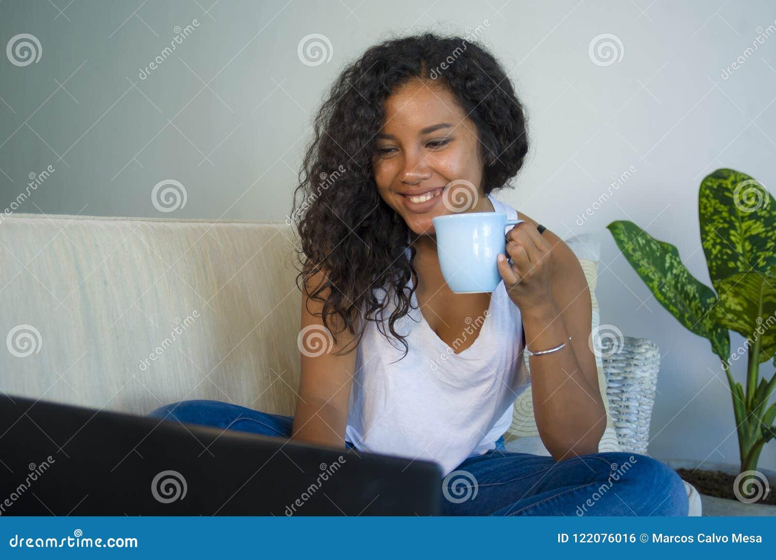 Mujer hispánica atractiva y relajada joven del estudiante que sienta en casa establecimiento de una red del sofá del sofá con caf