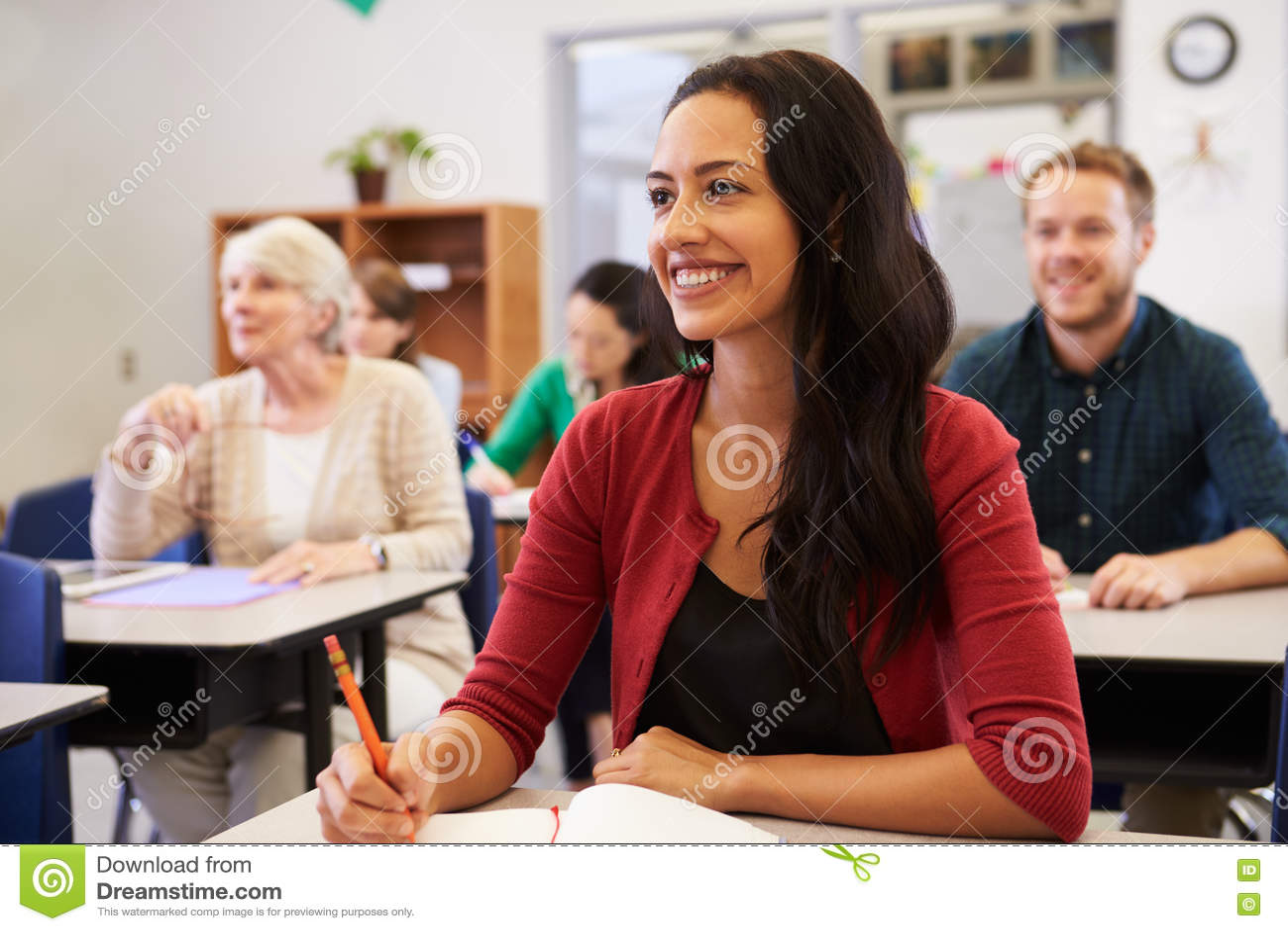Mujer hispánica que estudia en la clase de la enseñanza para adultos que mira para arriba