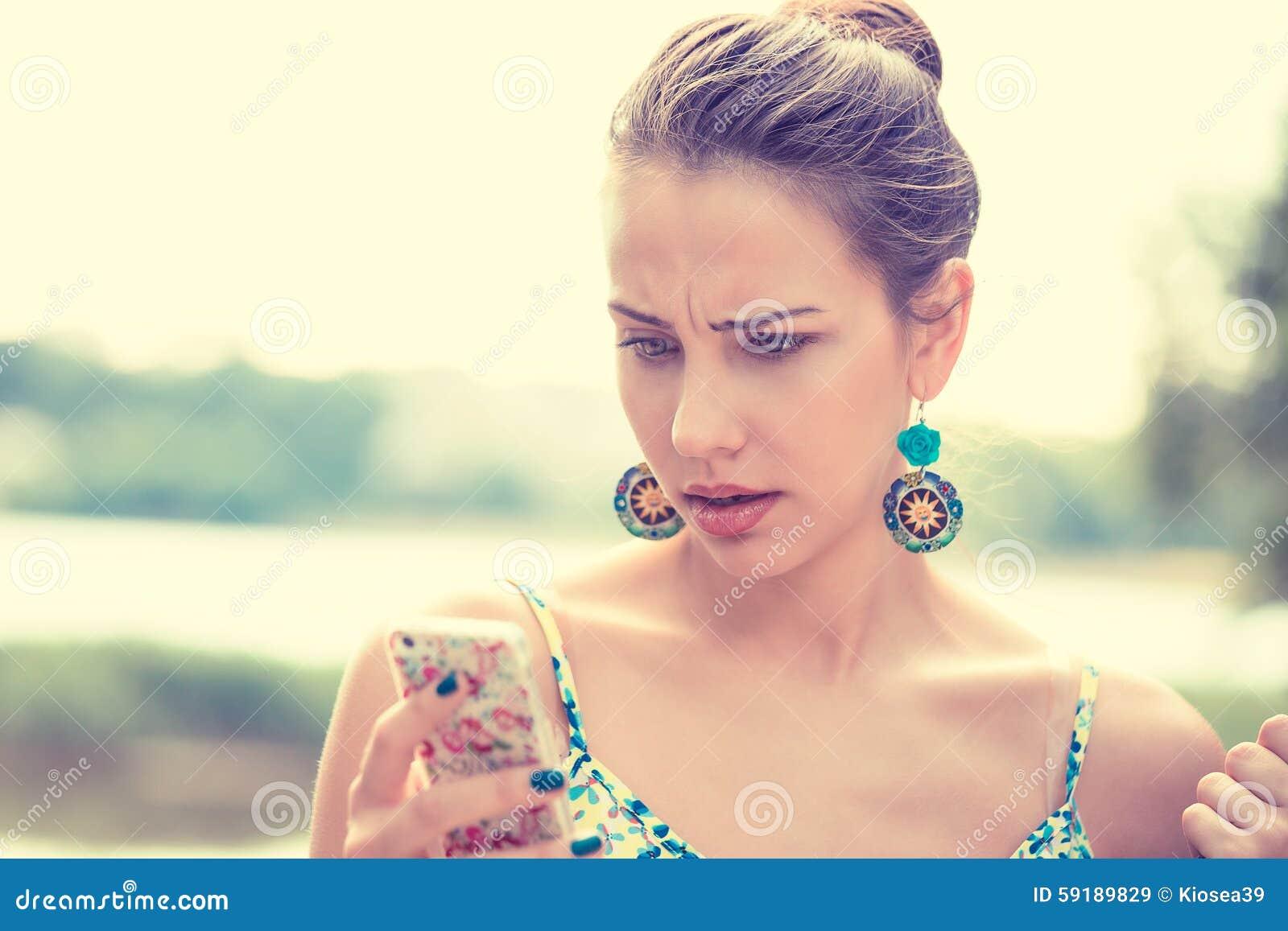 Mujer infeliz escéptica triste trastornada que manda un SMS en el teléfono