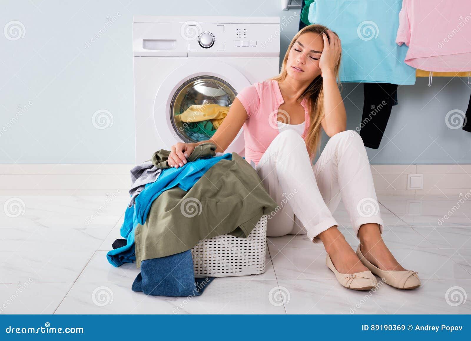 Mujer infeliz que mira la ropa en lavadero