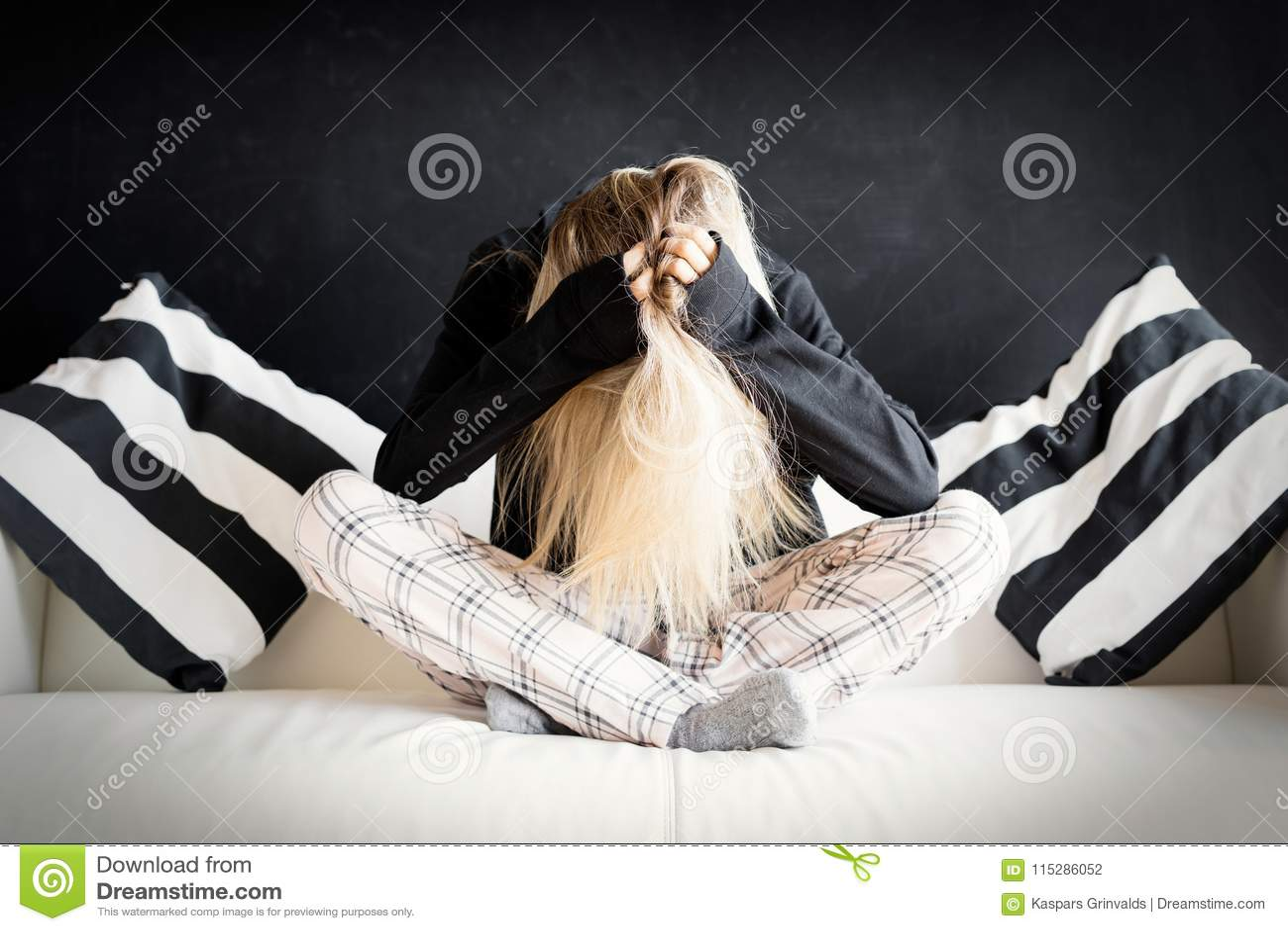 Mujer infeliz que se sienta en sofá