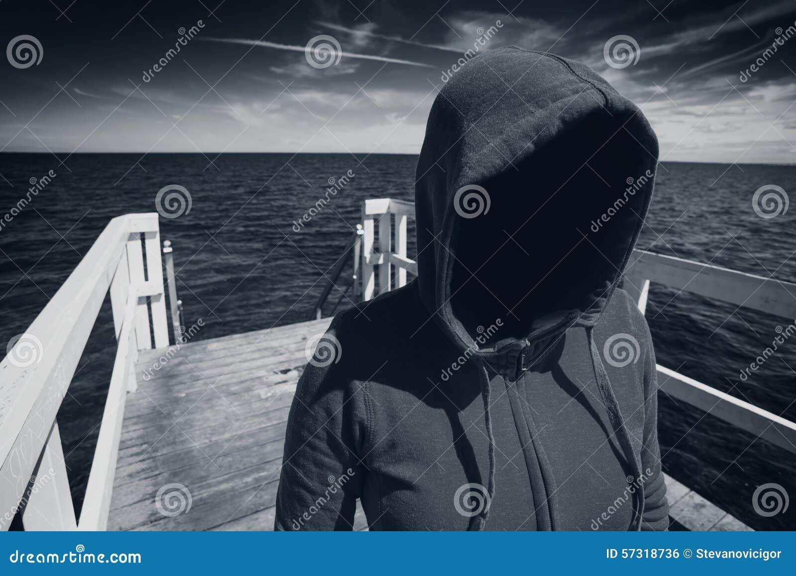 Mujer irreconocible encapuchada anónima en el embarcadero del océano, abducción Co