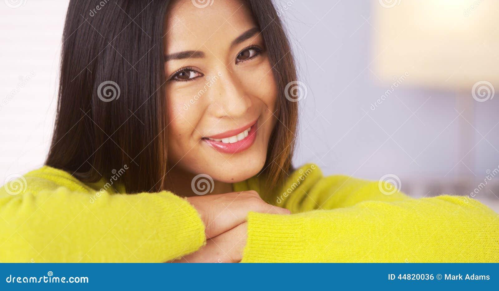 Mujer japonesa que sonríe en la cámara