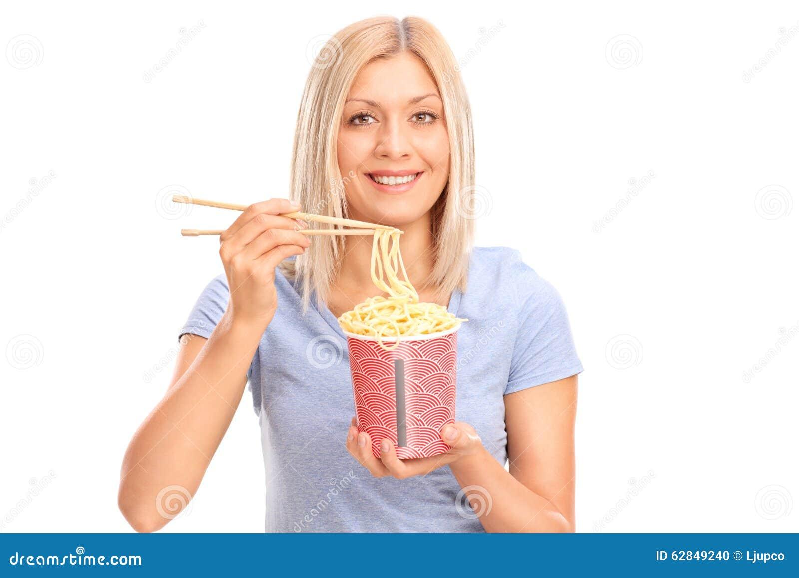Mujer joven alegre que come los tallarines