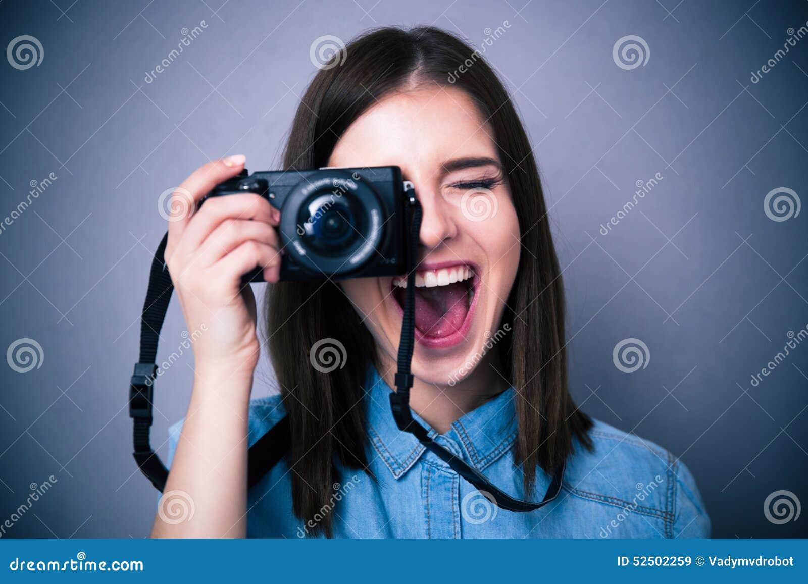Mujer joven alegre que hace la foto en cámara