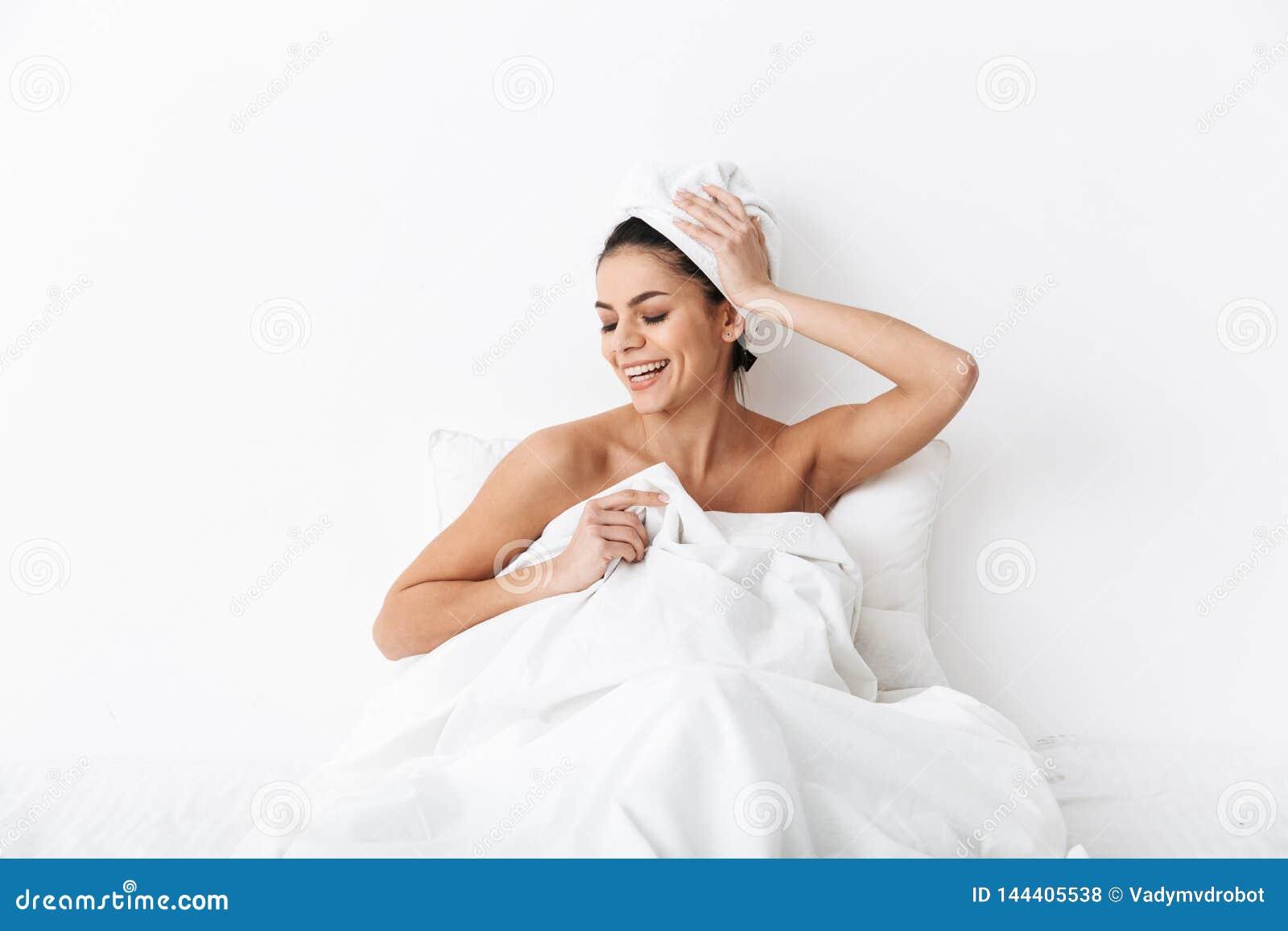 Mujer joven alegre que se sienta en cama despu?s de ducha