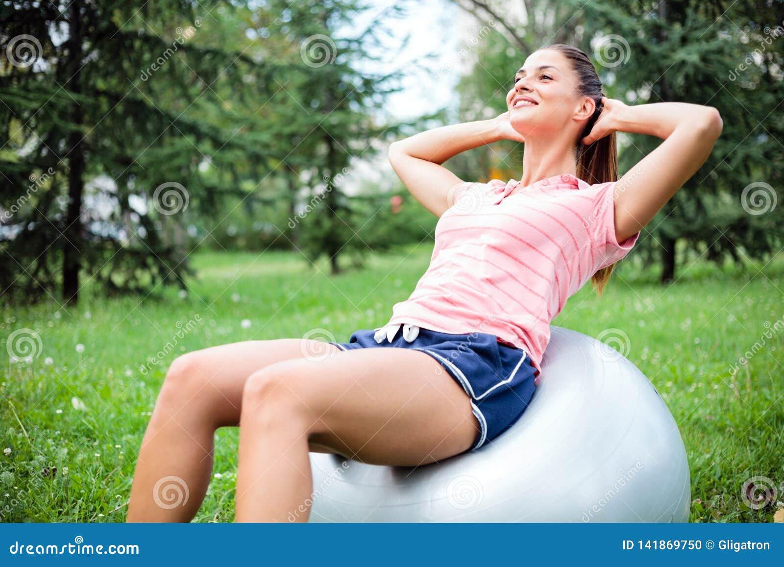 Mujer joven apta que hace sentar-UPS en una bola de la aptitud que ejercita en parque