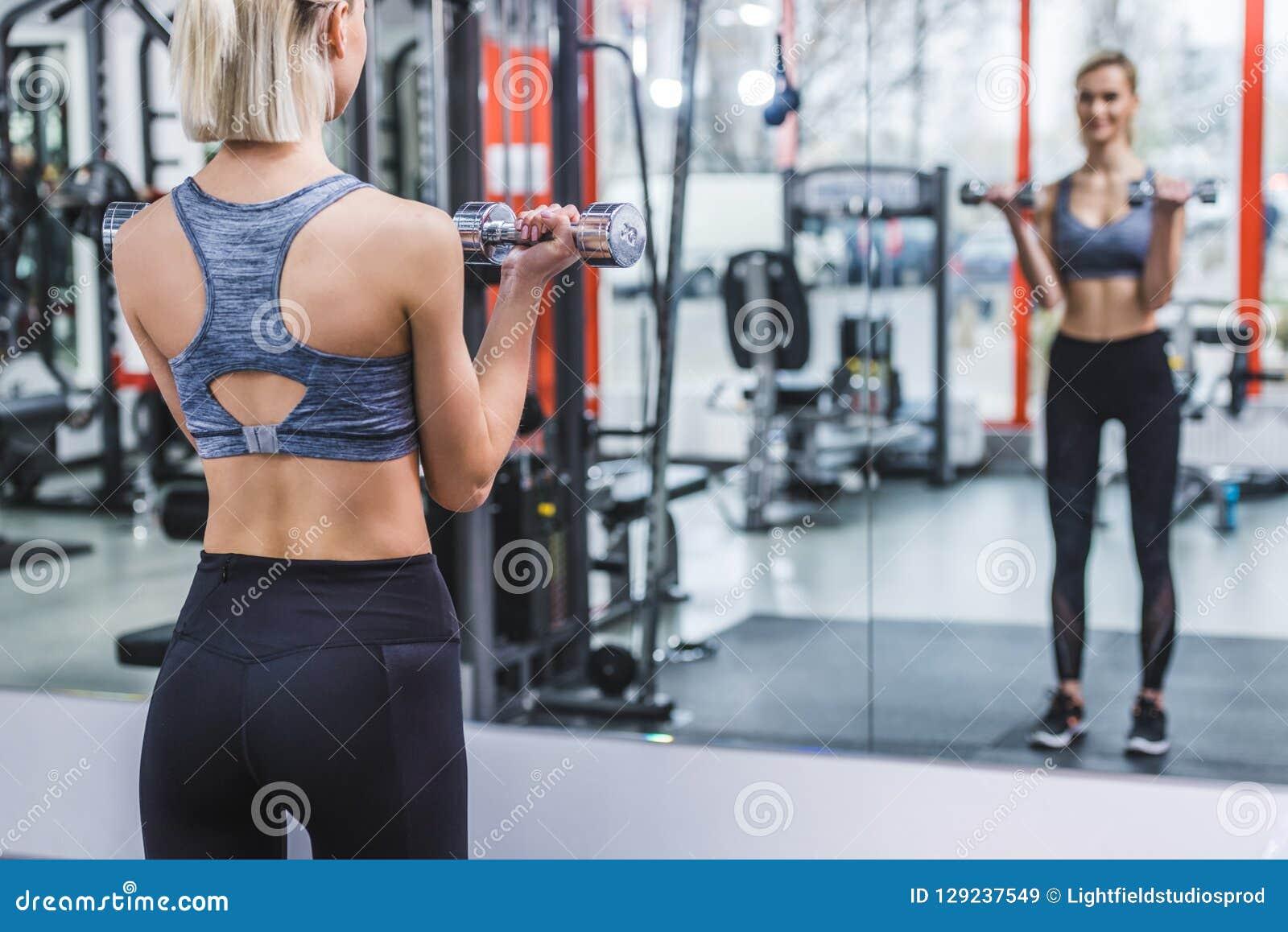 Mujer joven atlética que se resuelve con pesas de gimnasia delante del espejo