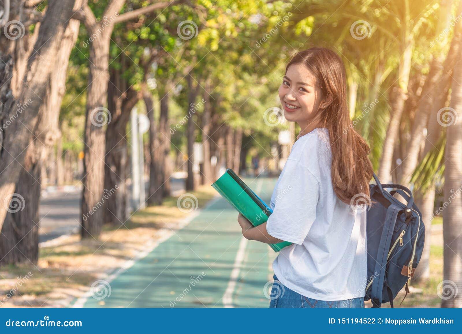 Mujer joven atractiva alegre con la mochila y el cuaderno y situación en el parque