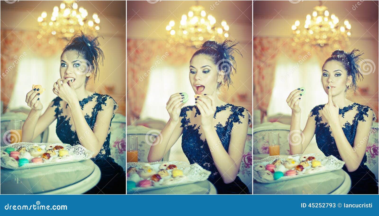 Mujer joven atractiva de moda en vestido negro que come los macarrones en restaurante Morenita hermosa que sostiene las galletas