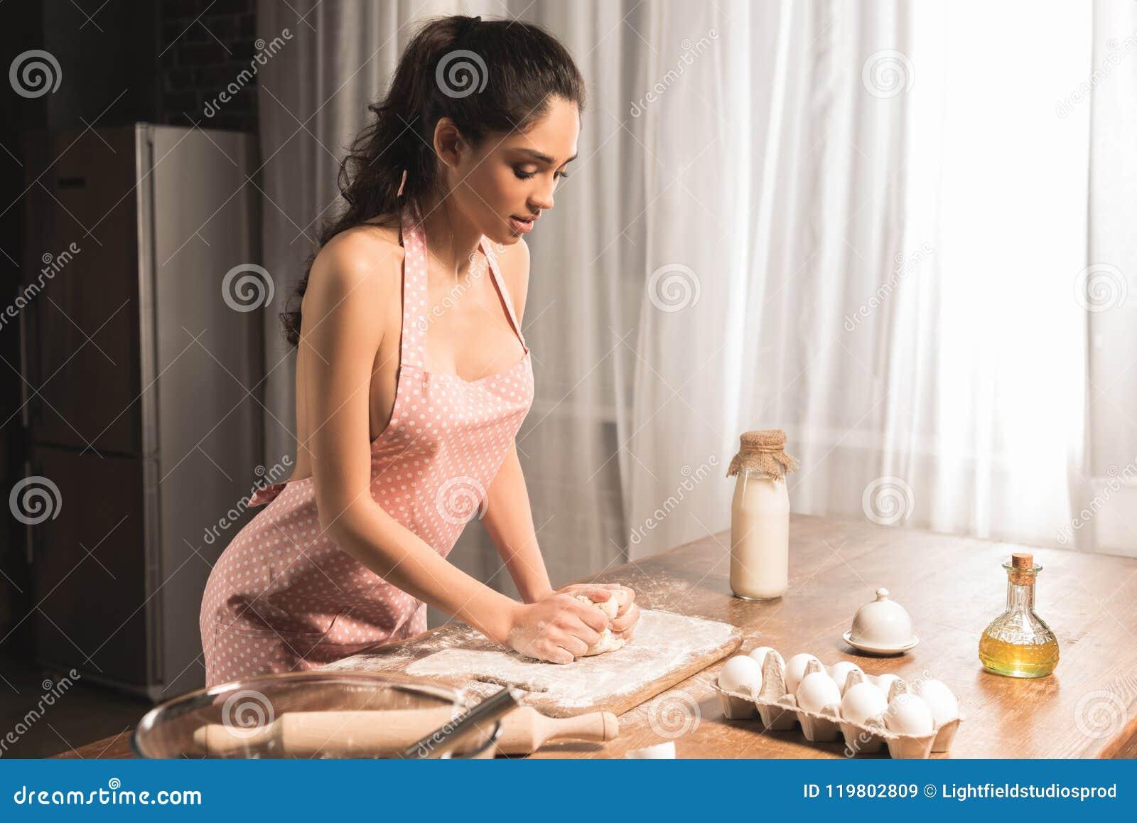 Mujer joven atractiva en el delantal que prepara la pasta