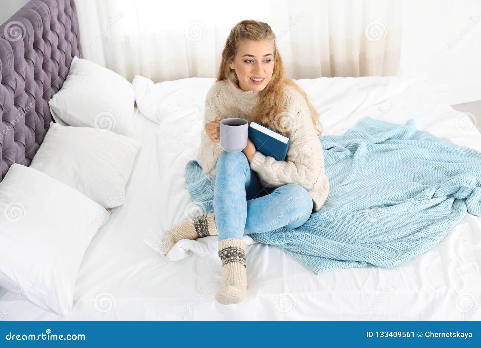 Mujer joven atractiva en suéter caliente acogedor con la taza de bebida caliente y el libro que se sienta en cama