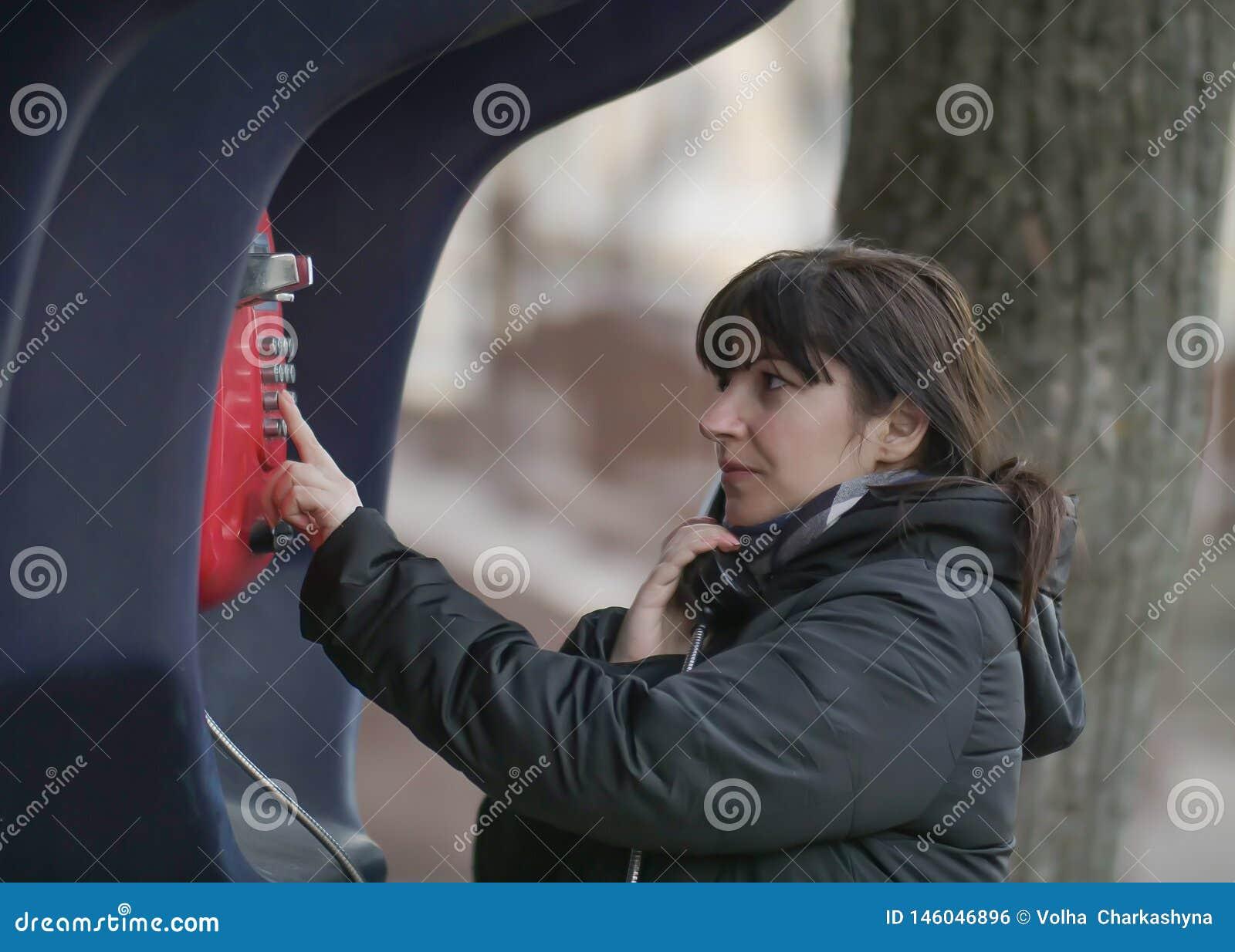 Mujer joven atractiva que llama de un teléfono público rojo de la calle