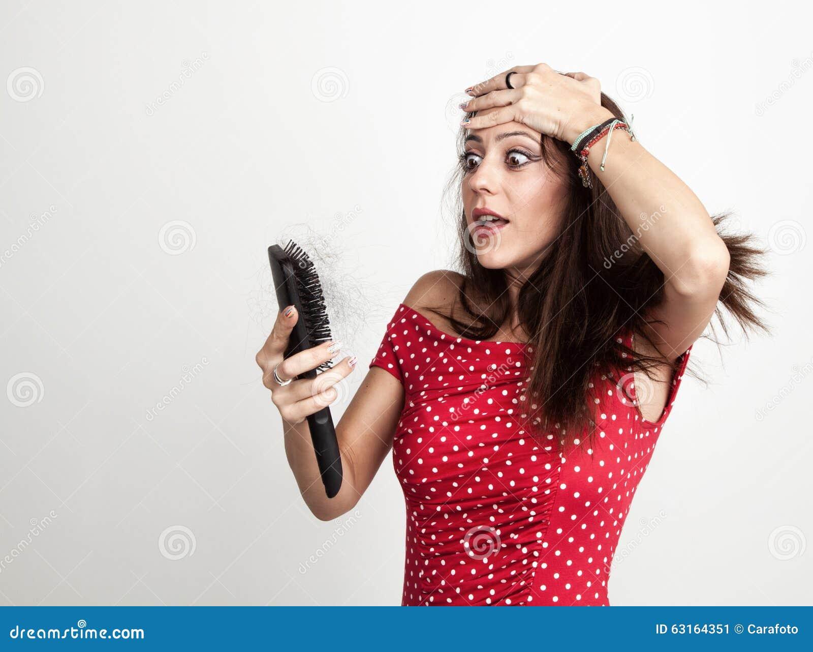 Mujer joven chocada con el cepillo de pelo