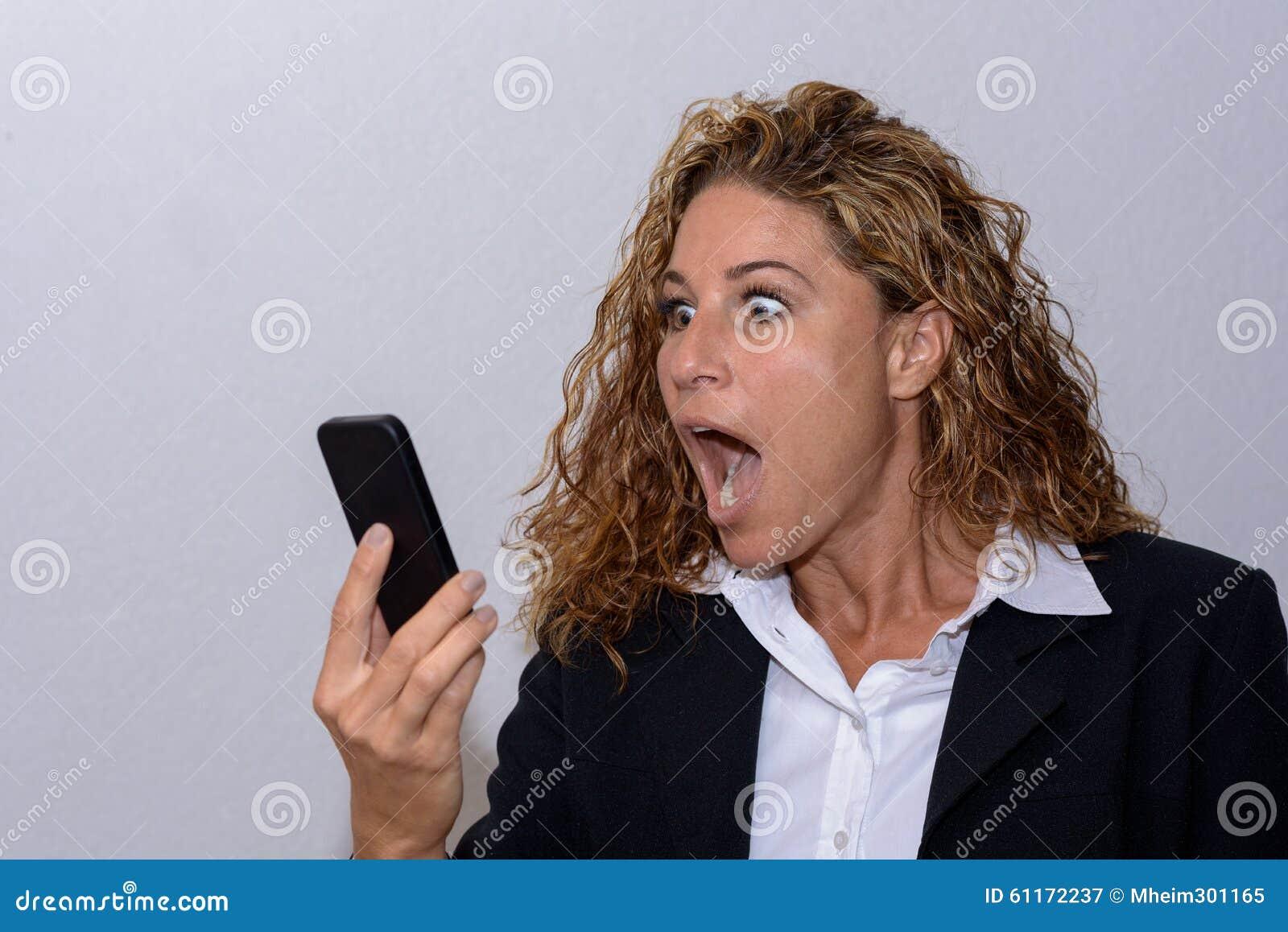 Mujer joven chocada que mira fijamente su móvil